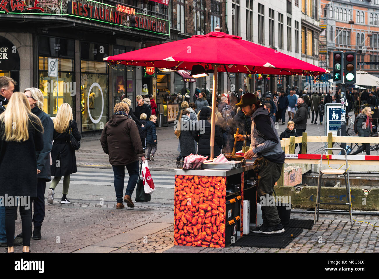 Copenhagen - October 17, 2016: On Nygade Street, a street merchant is frying some nuts for selling those and tourists Stock Photo