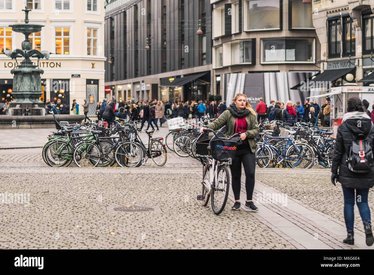 Copenhagen - October 17, 2016: Girls passing by the Local bicycle parking spot in the Amargertorv square. Stock Photo