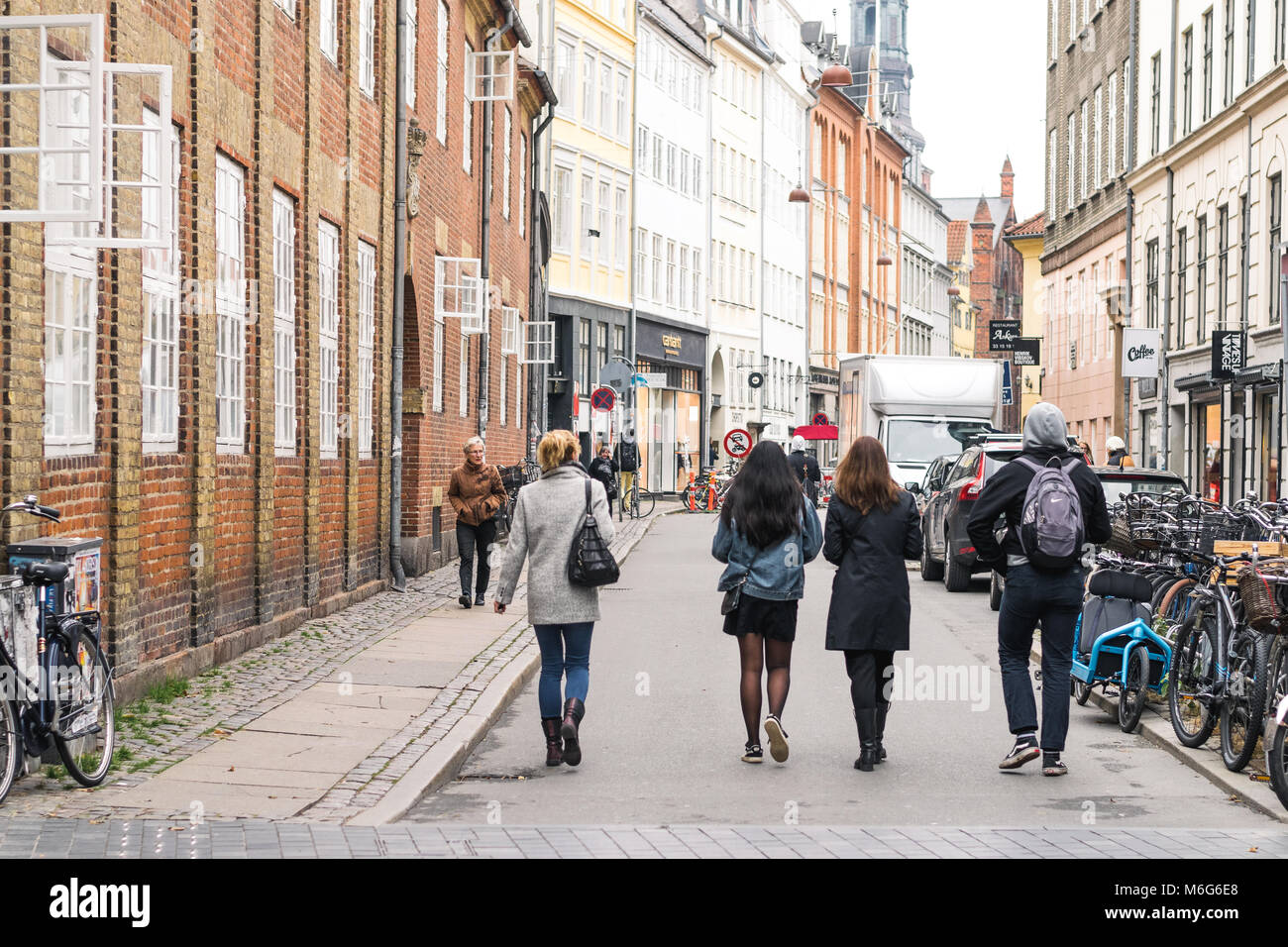 Copenhagen - October 17, 2016: Some passers by on Krystalgade street with a lot of bicycles parked nearby. Stock Photo