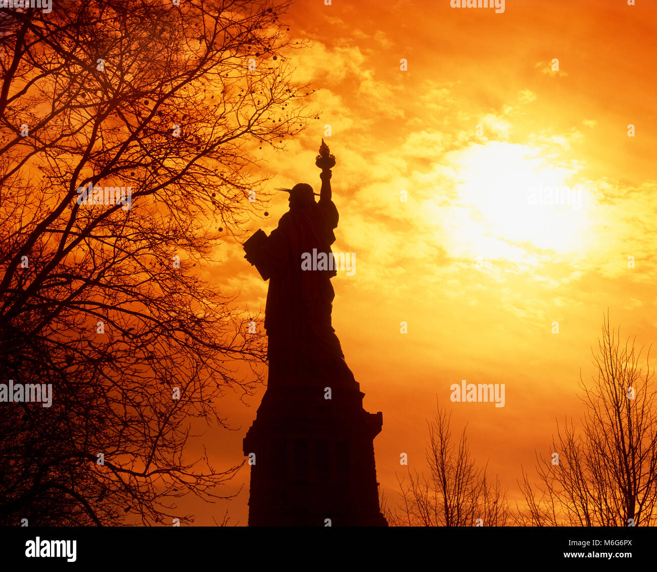 Silhouette of the Statue of Liberty at sunset, New York, USA - Stock Image