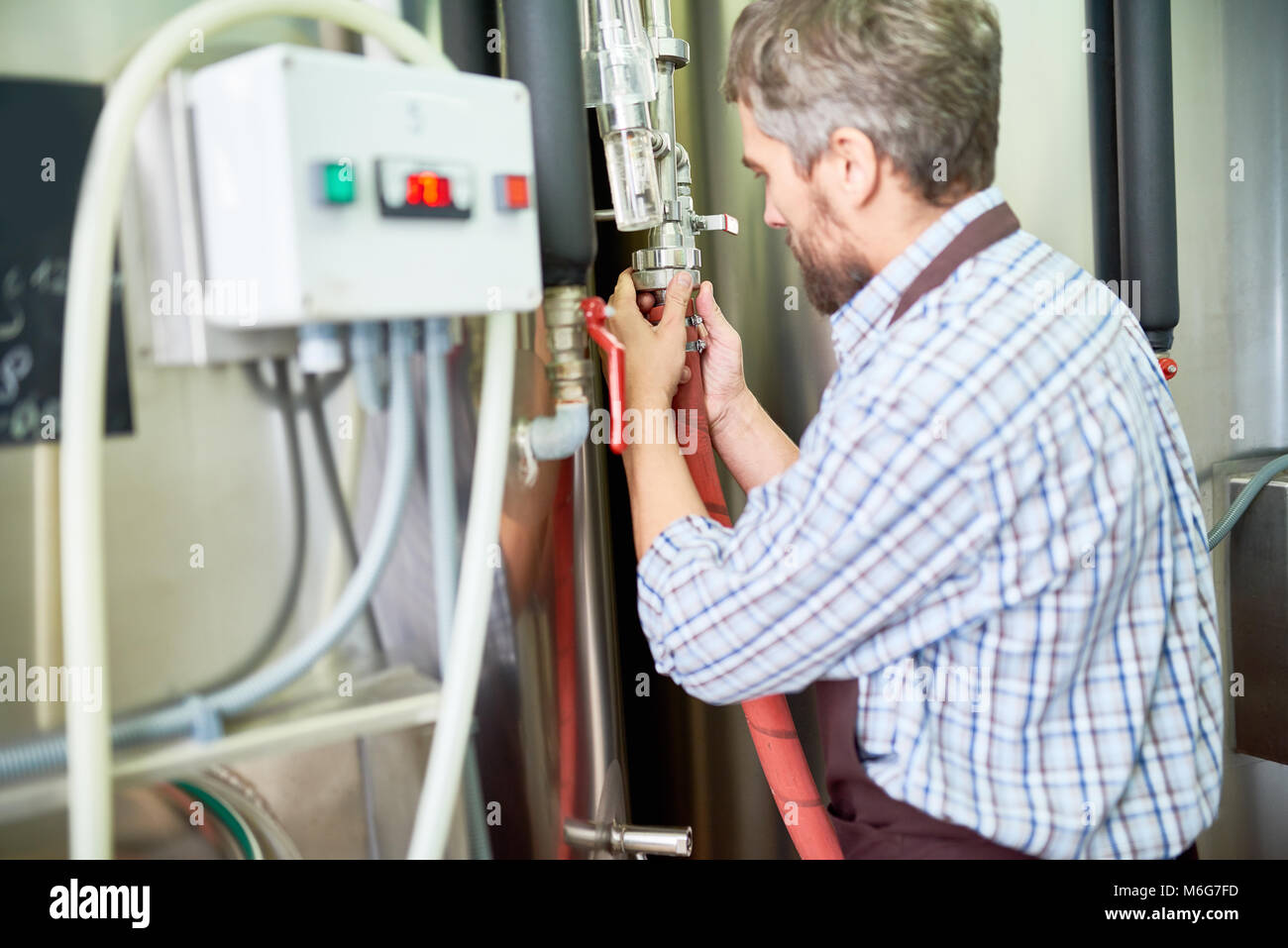 Bearded Technician Adjusting Equipment - Stock Image