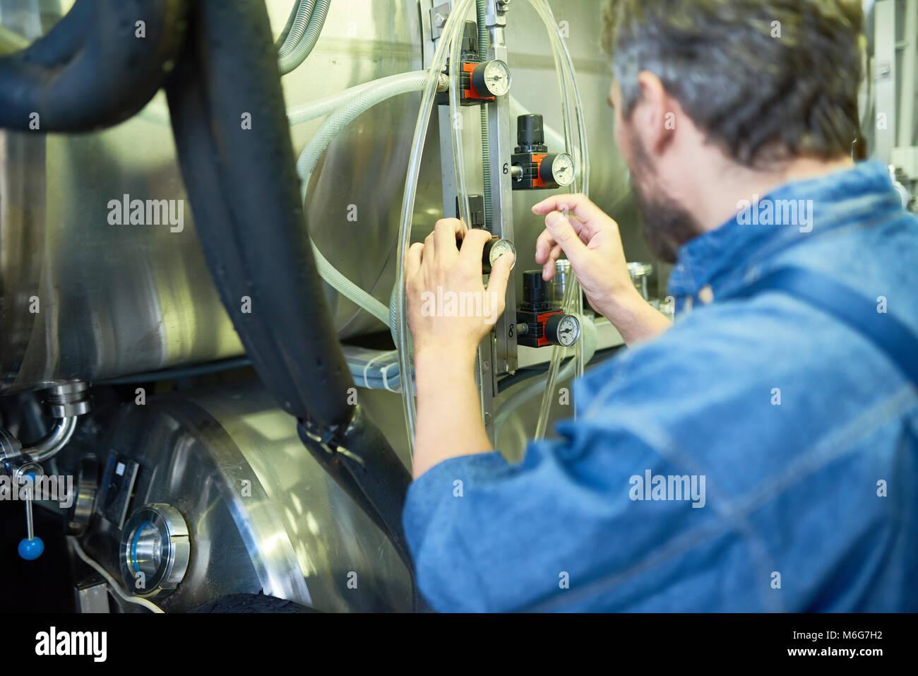 Bearded Brewer Adjusting Pressure - Stock Image