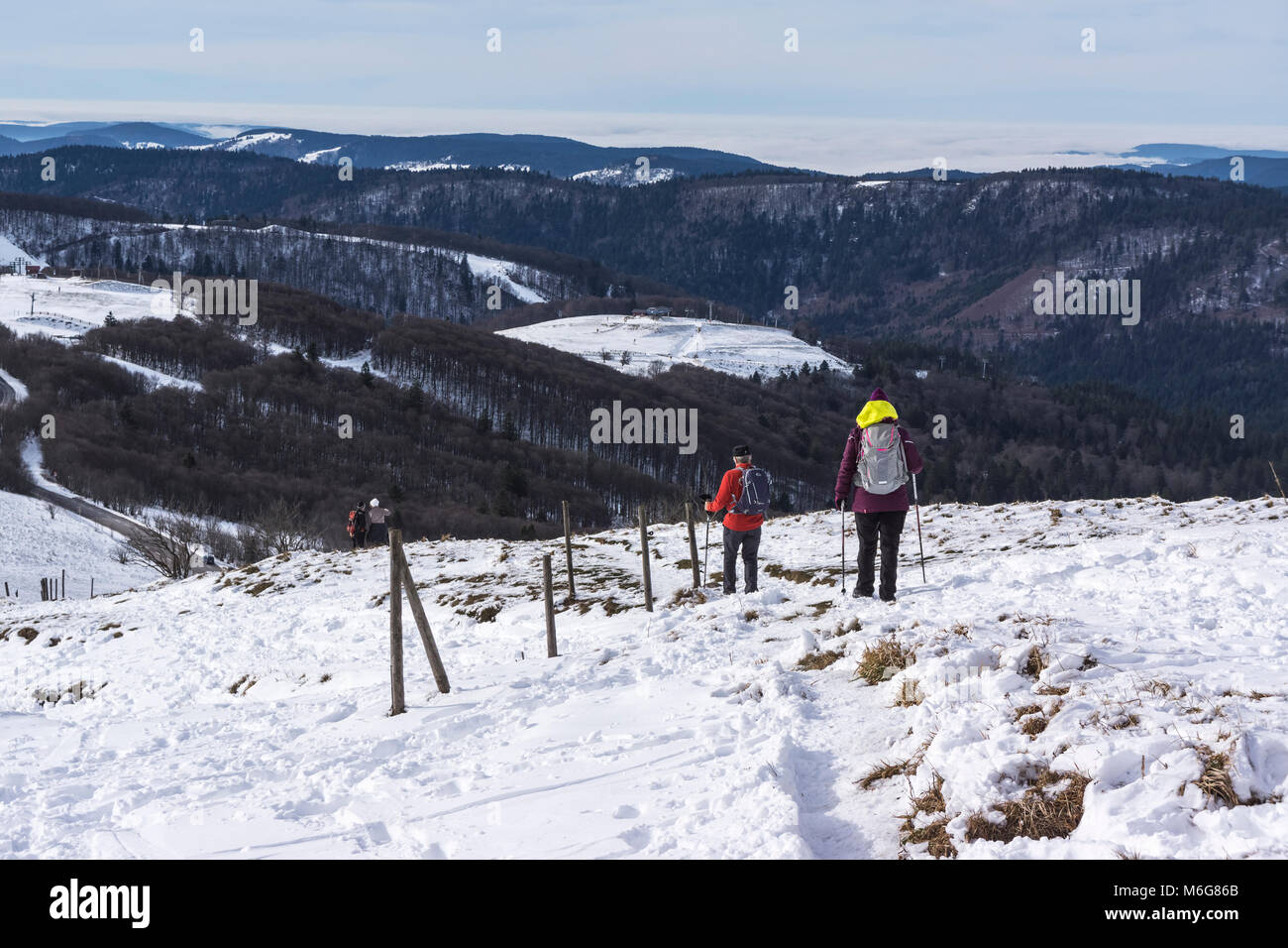 People hiking in the Vosges mountains in winter on a snowy ridge, Hohneck, France. - Stock Image