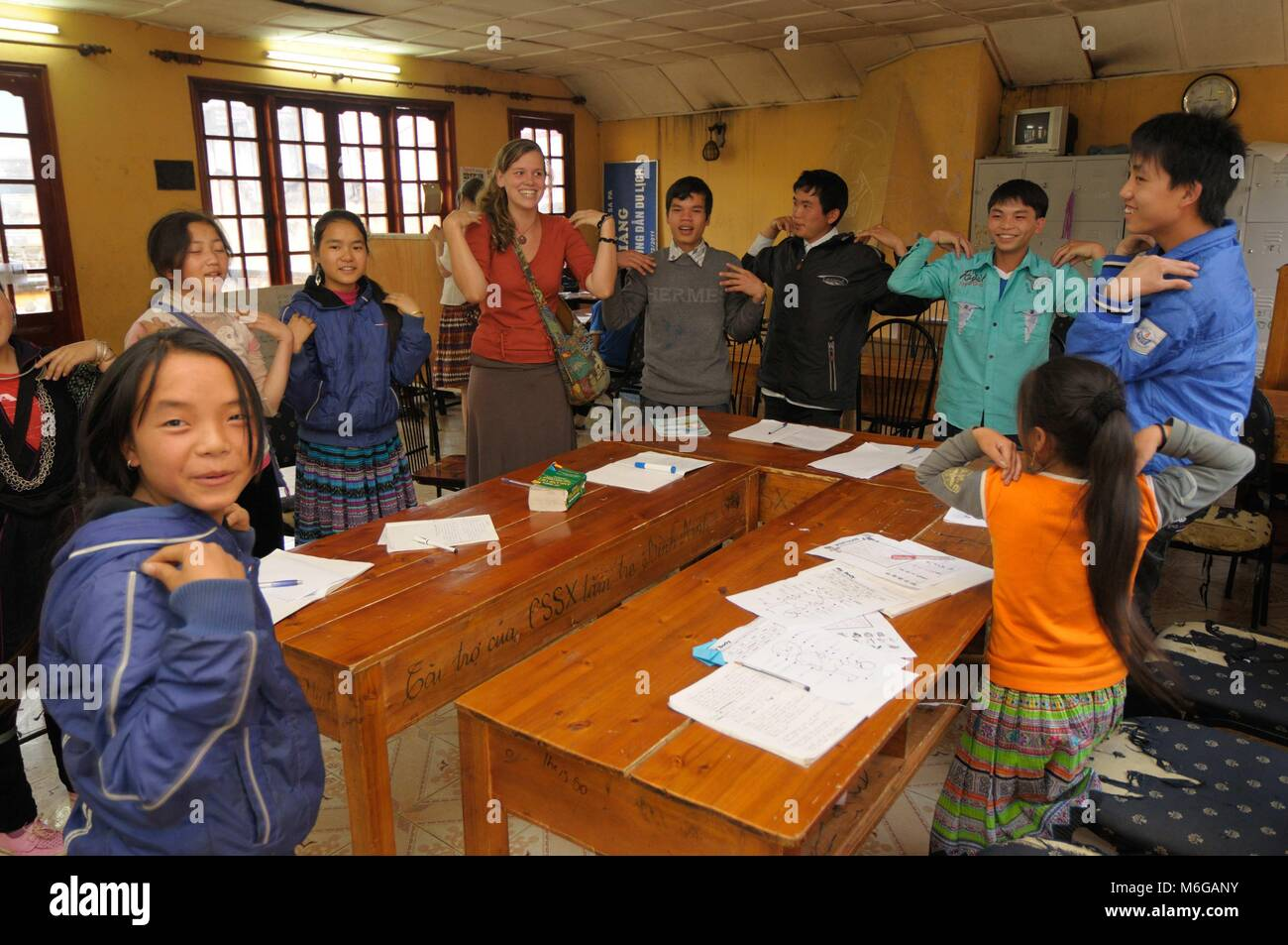 English language classroom in small school in Sapa Vietnam with young female teacher leading a group of Vietnamese Stock Photo