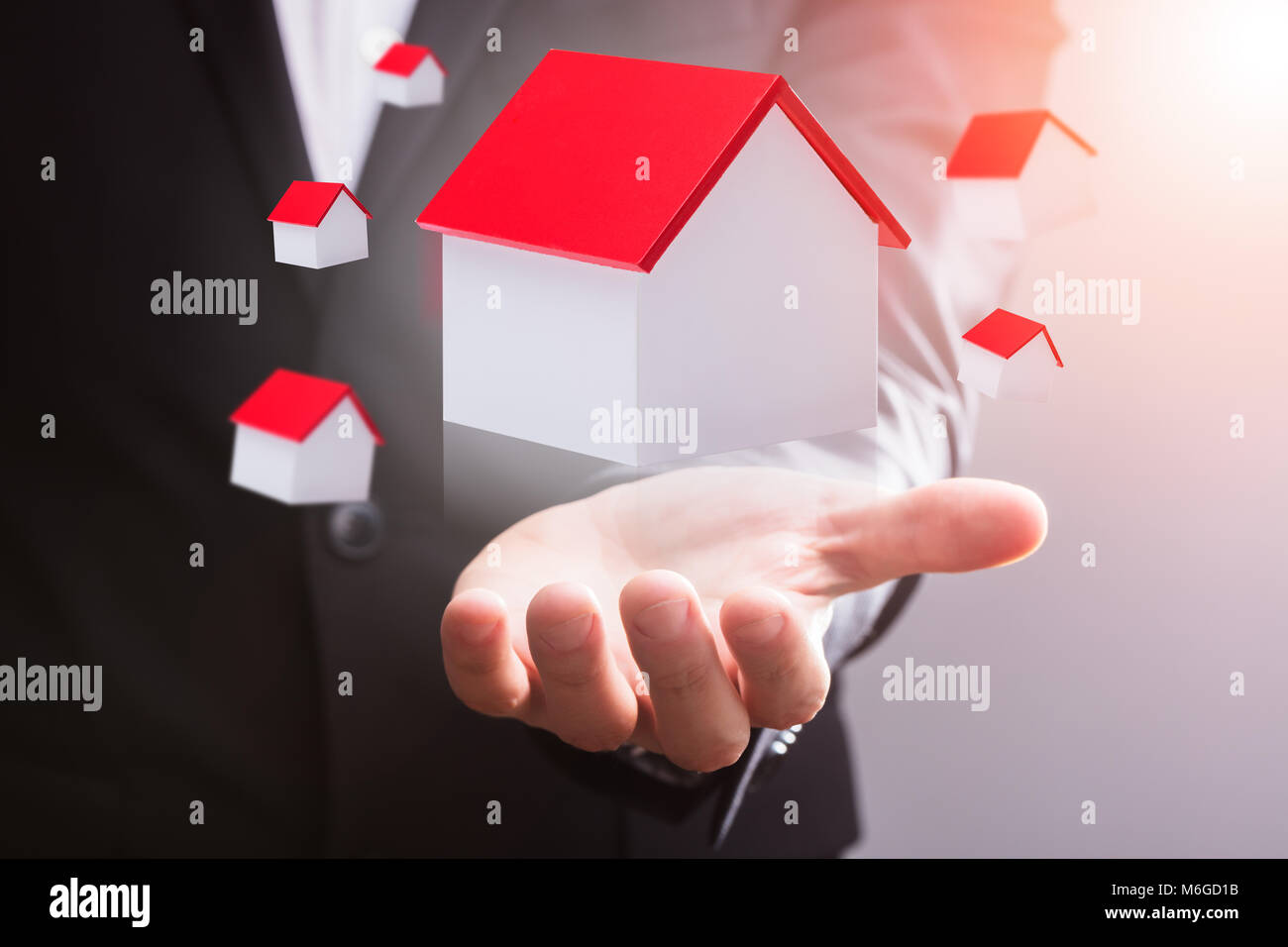 Close-up Of A House Models With Red Roof Floating In Mid-air Over Businessperson's Hand - Stock Image