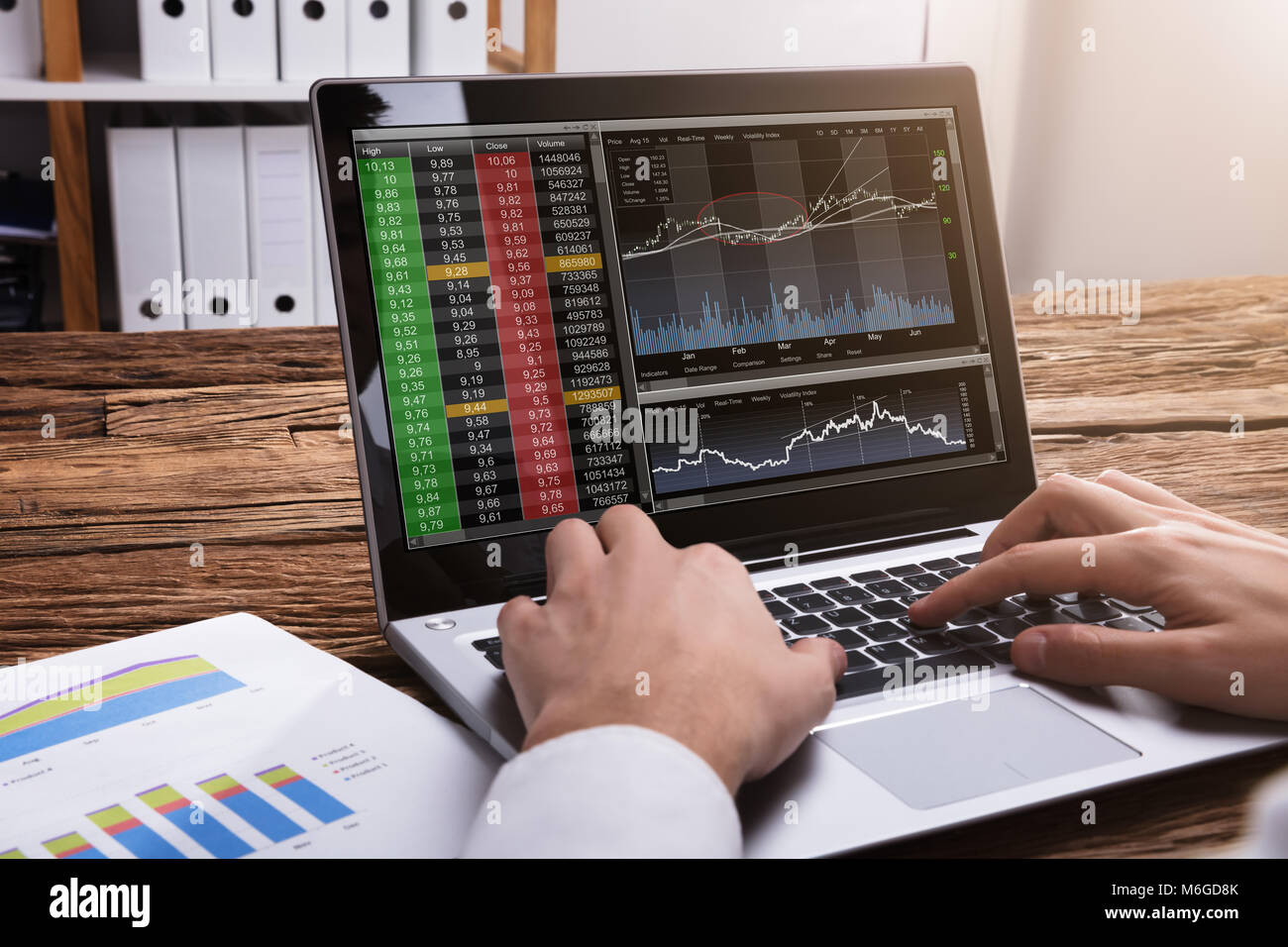 Close-up Of A Stock Market Broker's Hand Looking At Graphs On Laptop - Stock Image