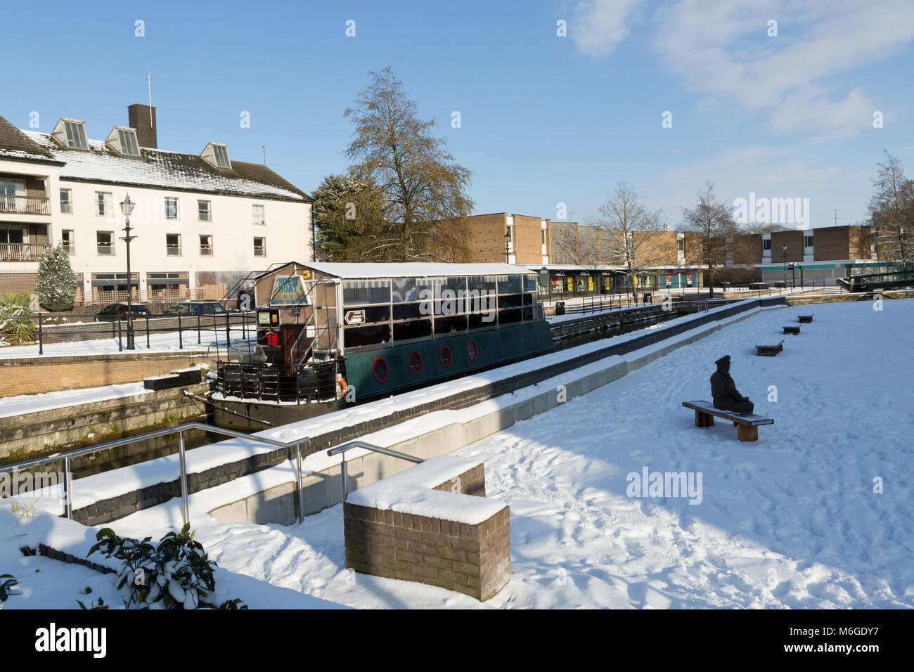 Little Ouse River at Thetford Riverside with boat restaurant, Bell Hotel and shops in distance. - Stock Image