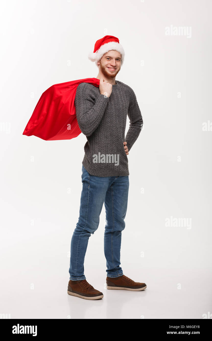 911bd8d52e724 Christmas concept - Young confident smart man holding red big santa bag  with a lot of present inside.