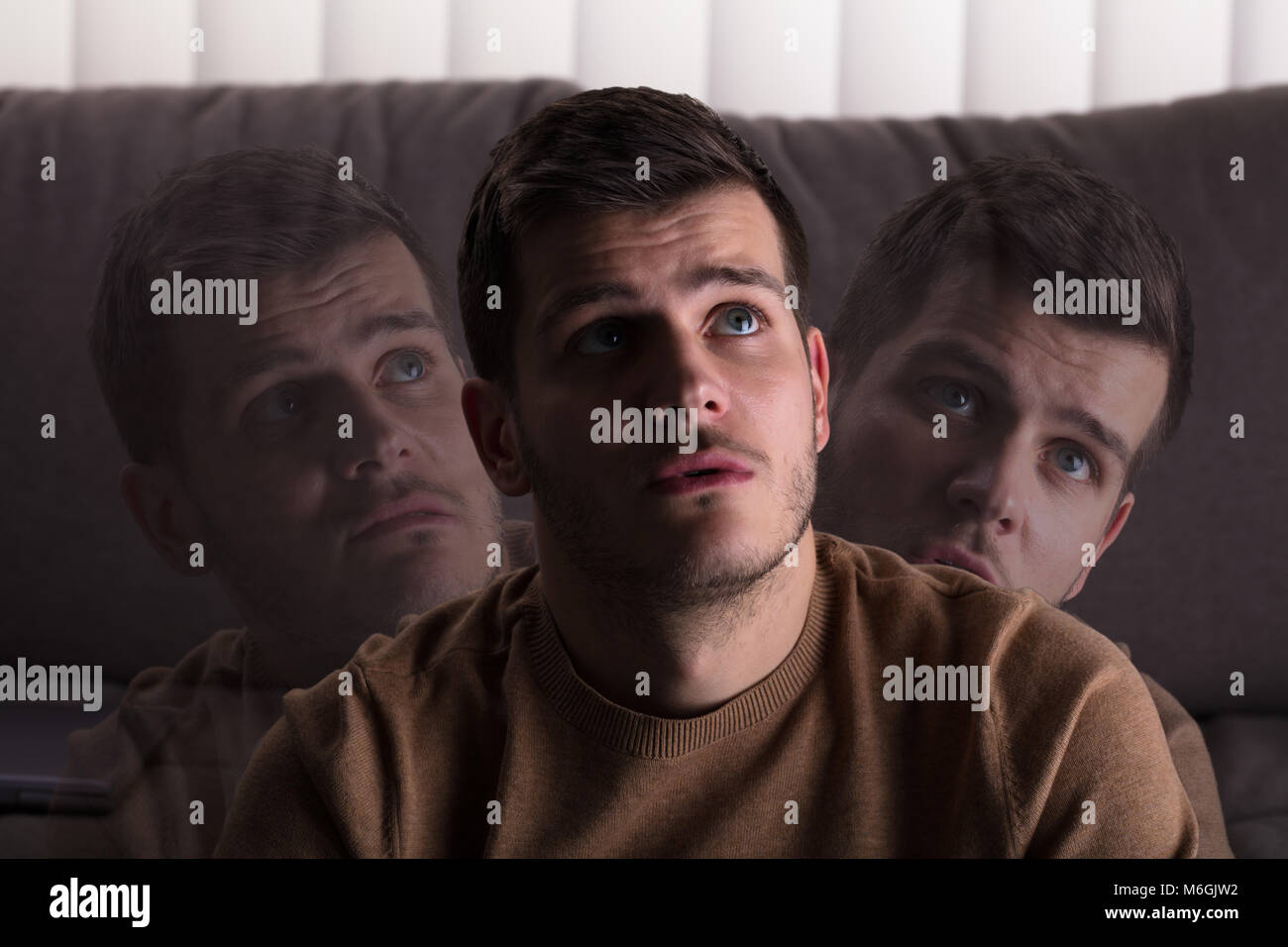 Multi Exposure Of Contemplated Man At Home - Stock Image