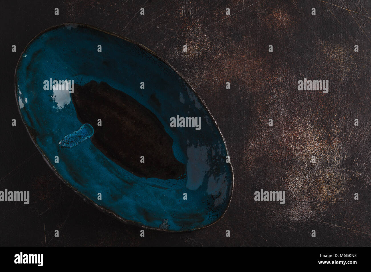 Beautiful empty blue plate on a dark rusty background. Copy space, top view. - Stock Image