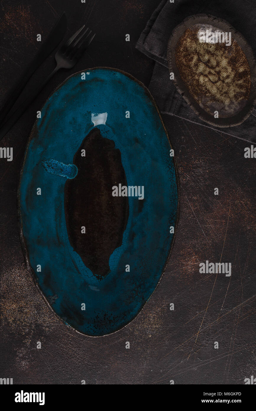 Beautiful vintage empty blue plates on a dark rusty background. Copy space, top view. - Stock Image