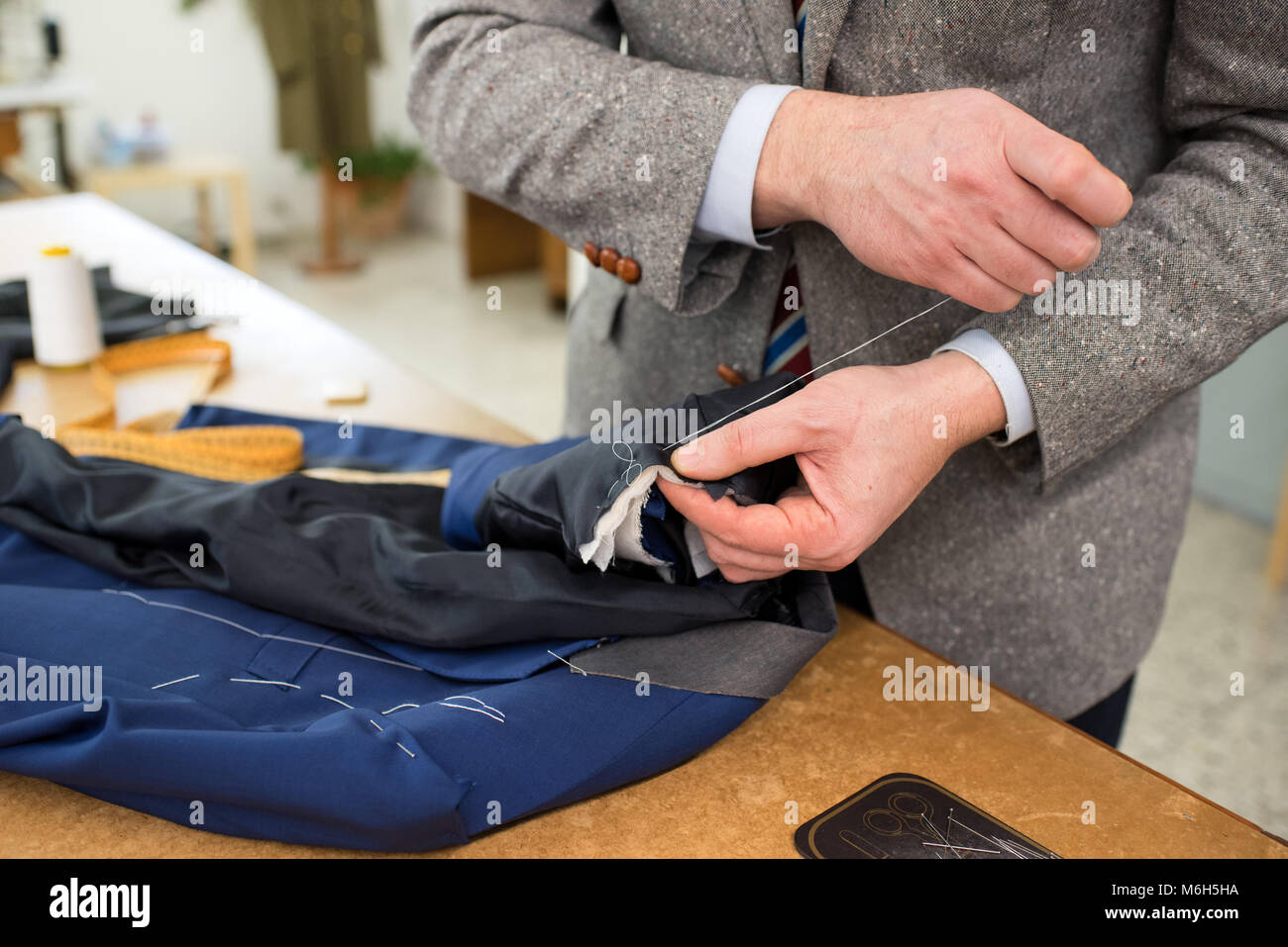 Work in progress with a tailor hand sewing a new blue jacket while standing at a work table in his workshop in a - Stock Image
