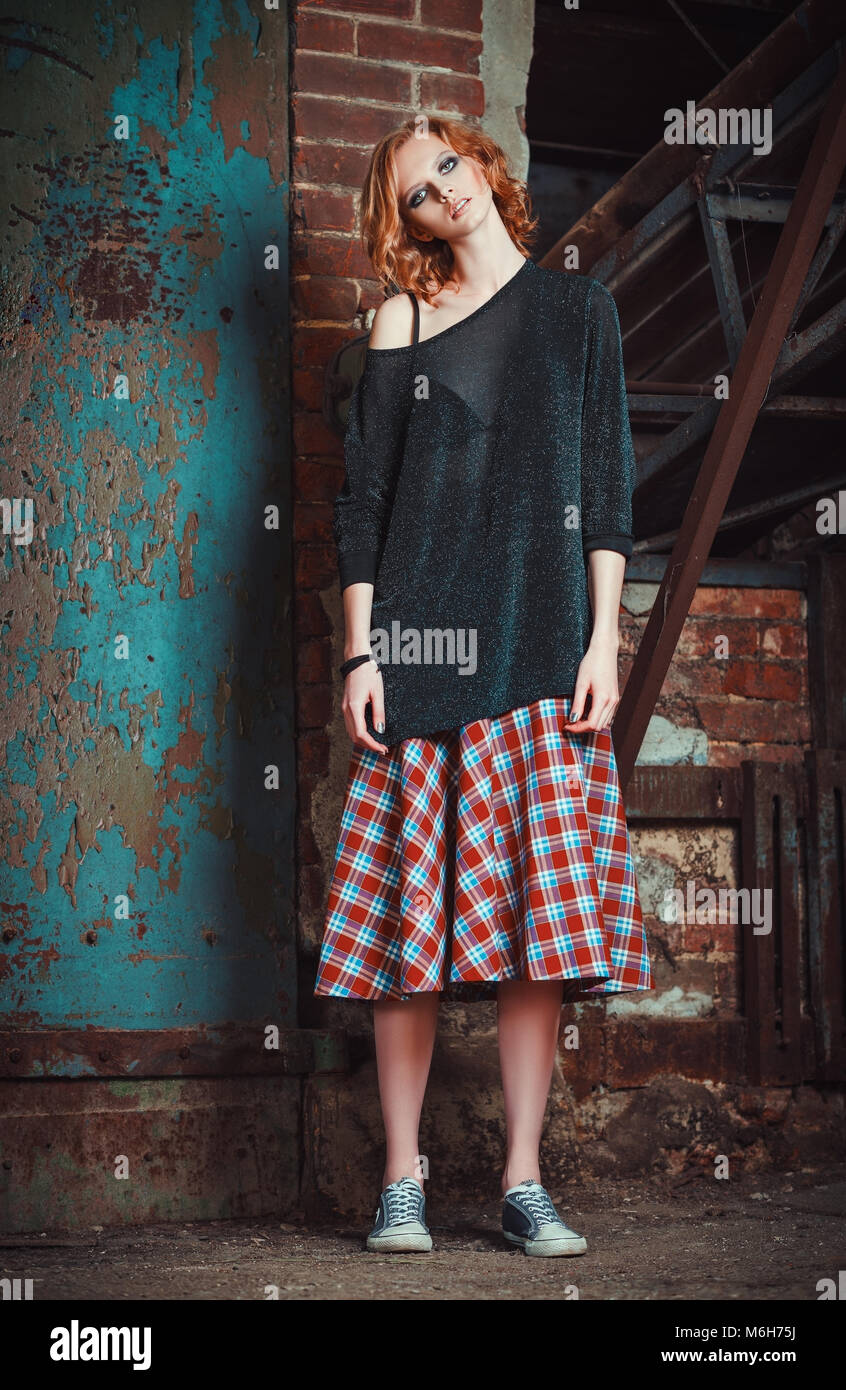 Grunge fashion: portrait of a beautiful young redhead girl in plaid skirt and sweater Stock Photo