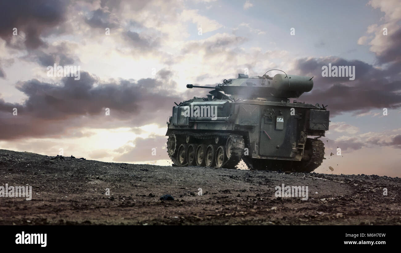 British Army FV432 tracked armoured personnel carrier heading away towards moody sky. Used in the Cold War and commonly - Stock Image