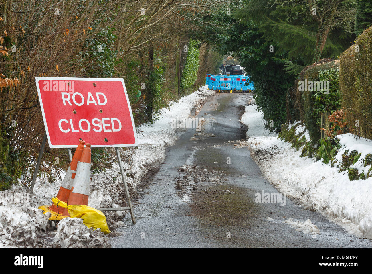 Road closure due to burst water main after heavy snowfall and freezing temperatures. Catbrook, Monmouthshire, Wales - Stock Image
