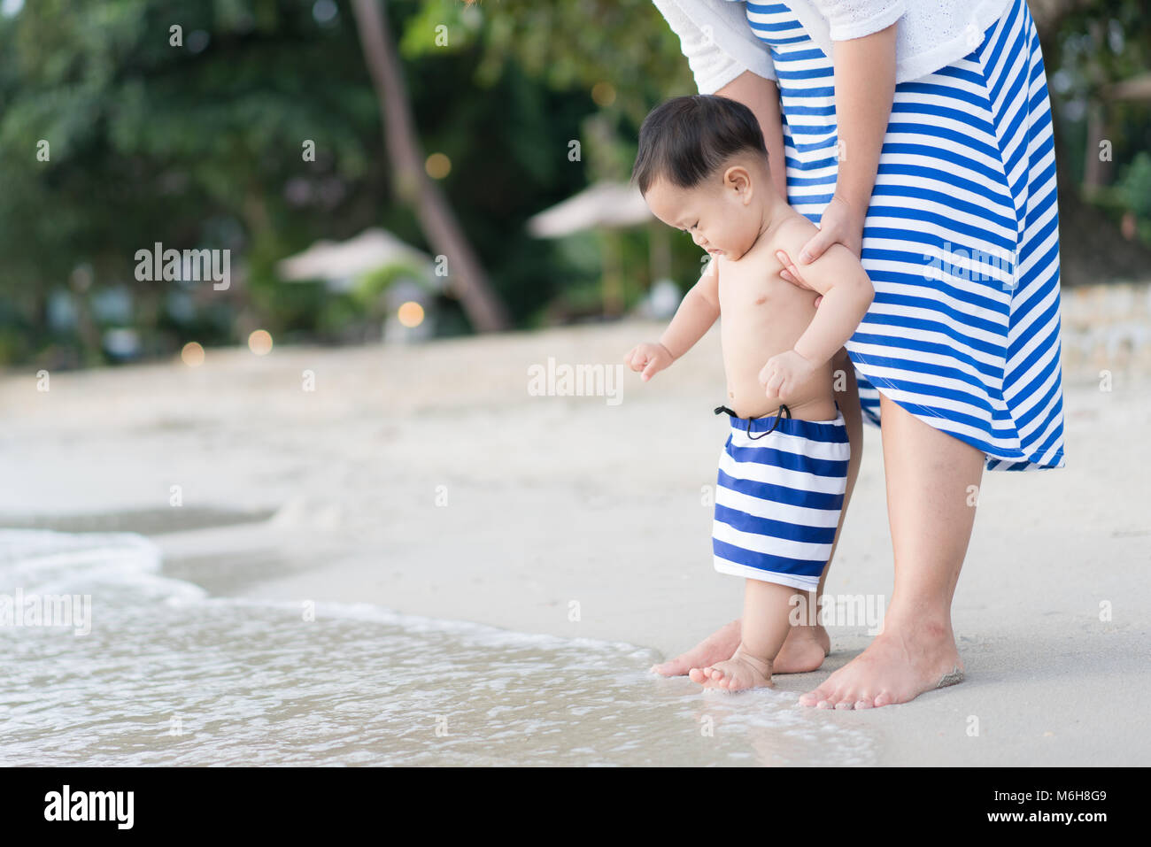 Asian Toddler baby boy with mother doing his first steps on the sand near the bank - Stock Image
