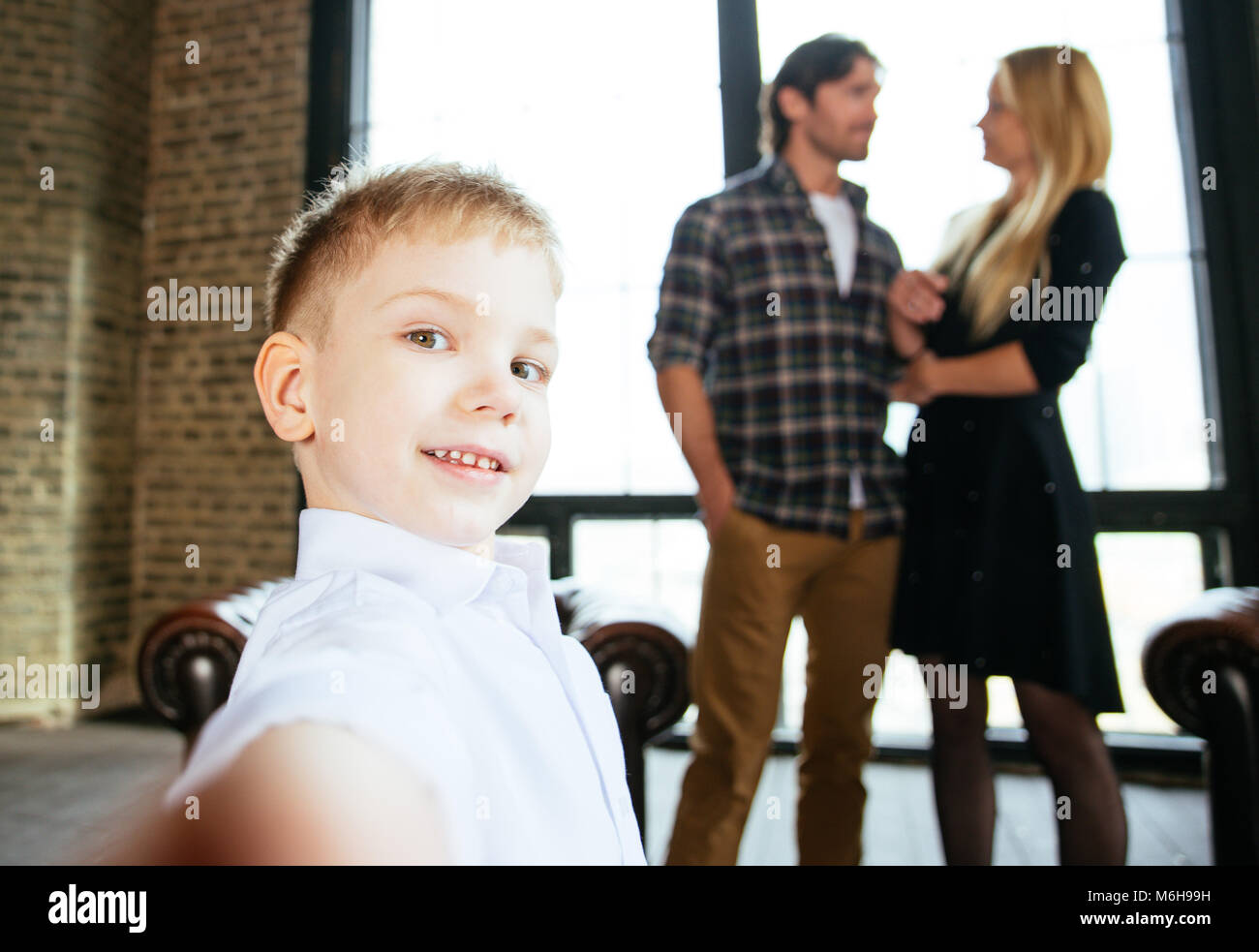 Family home portrait. Parents and son spending time together - Stock Image