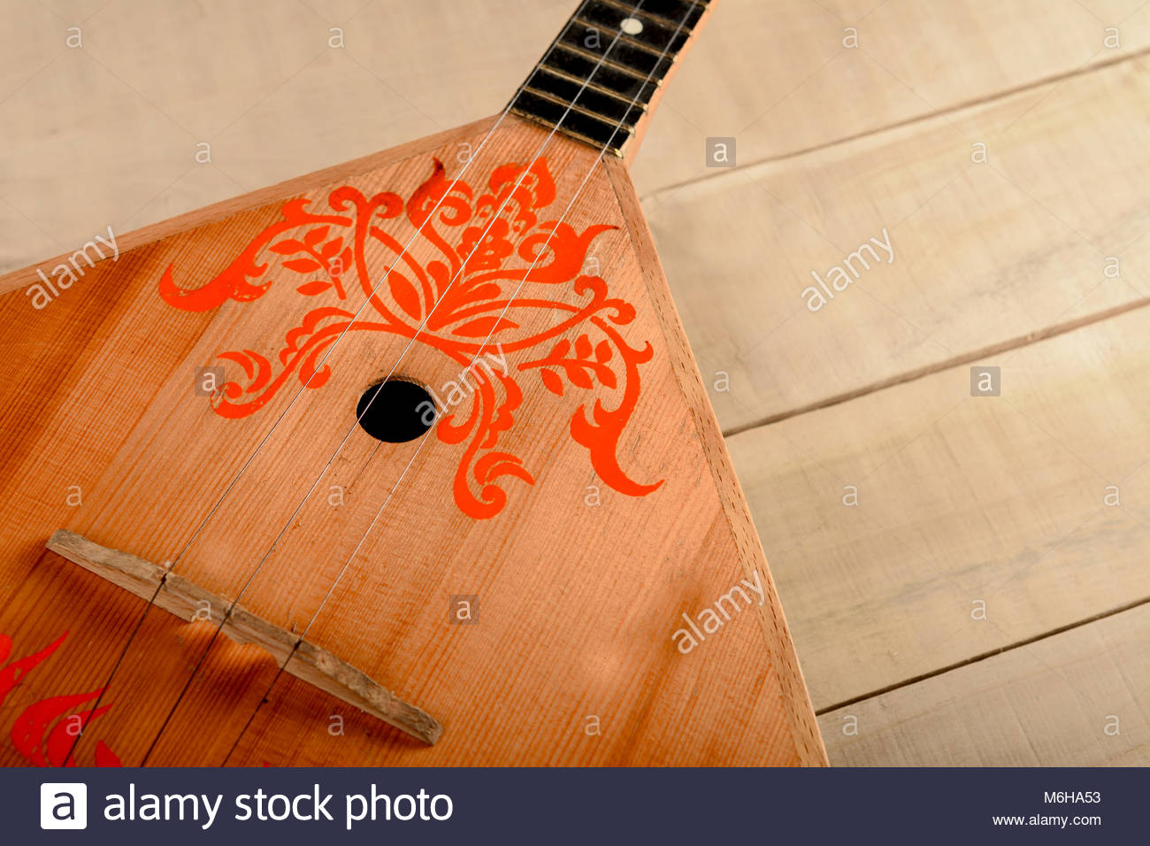 Photo Russian musical instrument balalaika on a wooden table - Stock Image