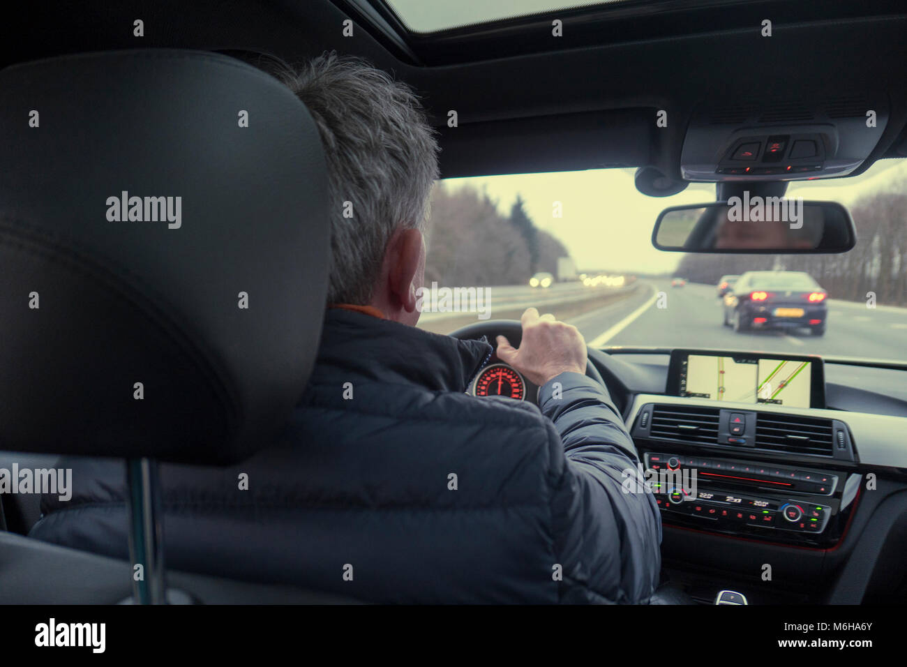 Man inside car driving on highway - Stock Image
