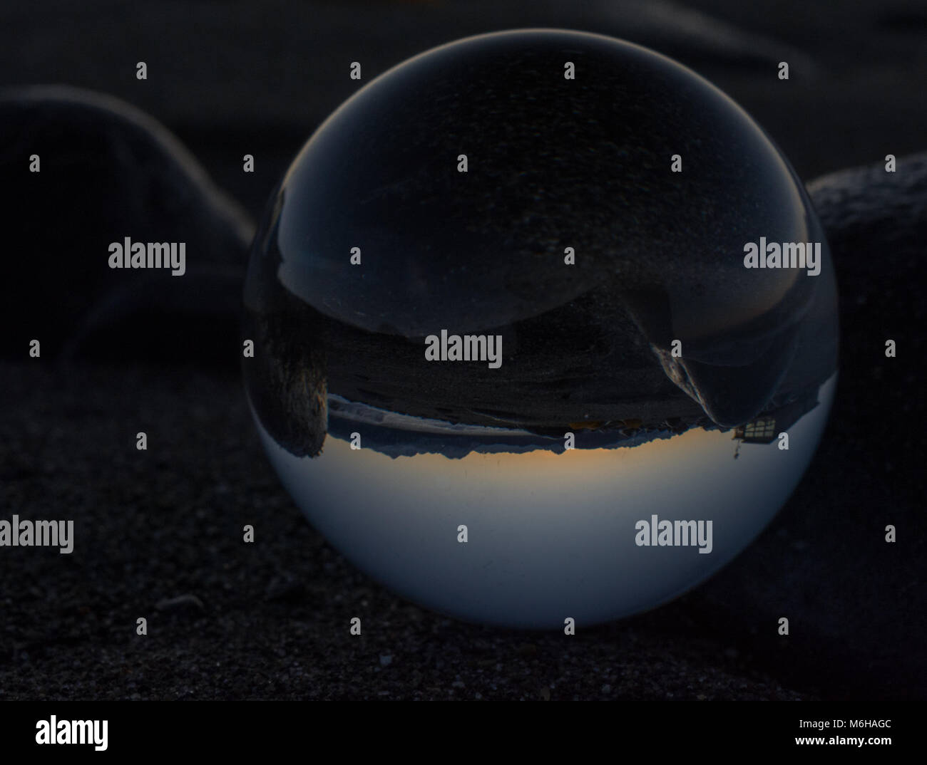 A crystal ball inverts the Homer beach at sunrise. - Stock Image