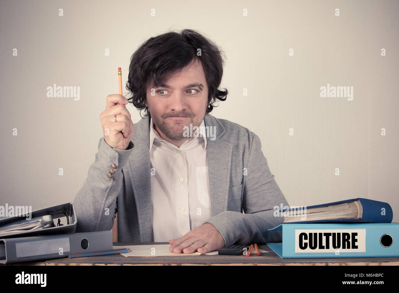 Culture text on the binder, worried bussinesman thinking by the work desk - Stock Image