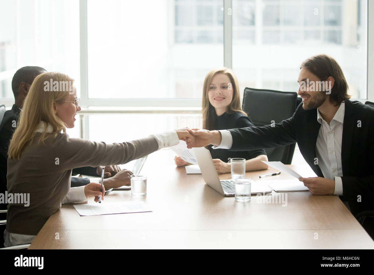 Smiling businessman and businesswoman shaking hands at diverse t - Stock Image