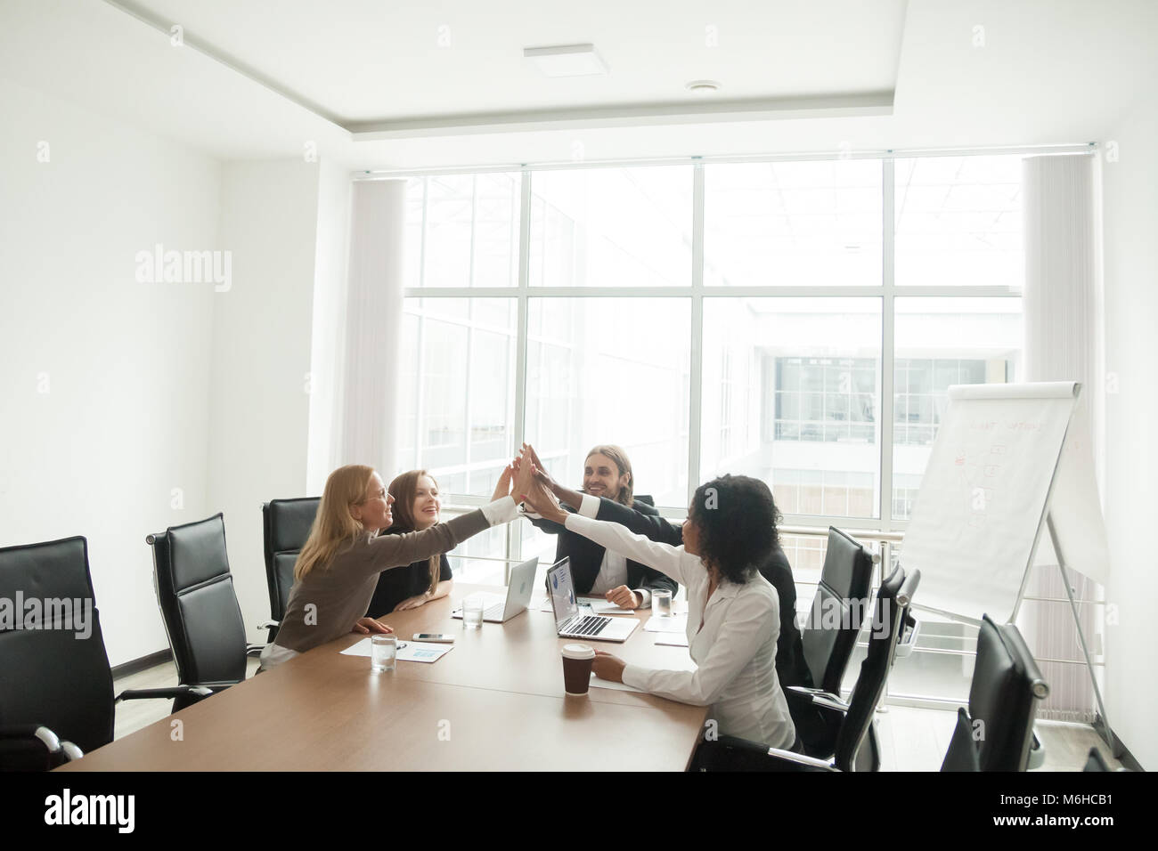 Happy businesspeople giving high-five at office meeting, celebra - Stock Image