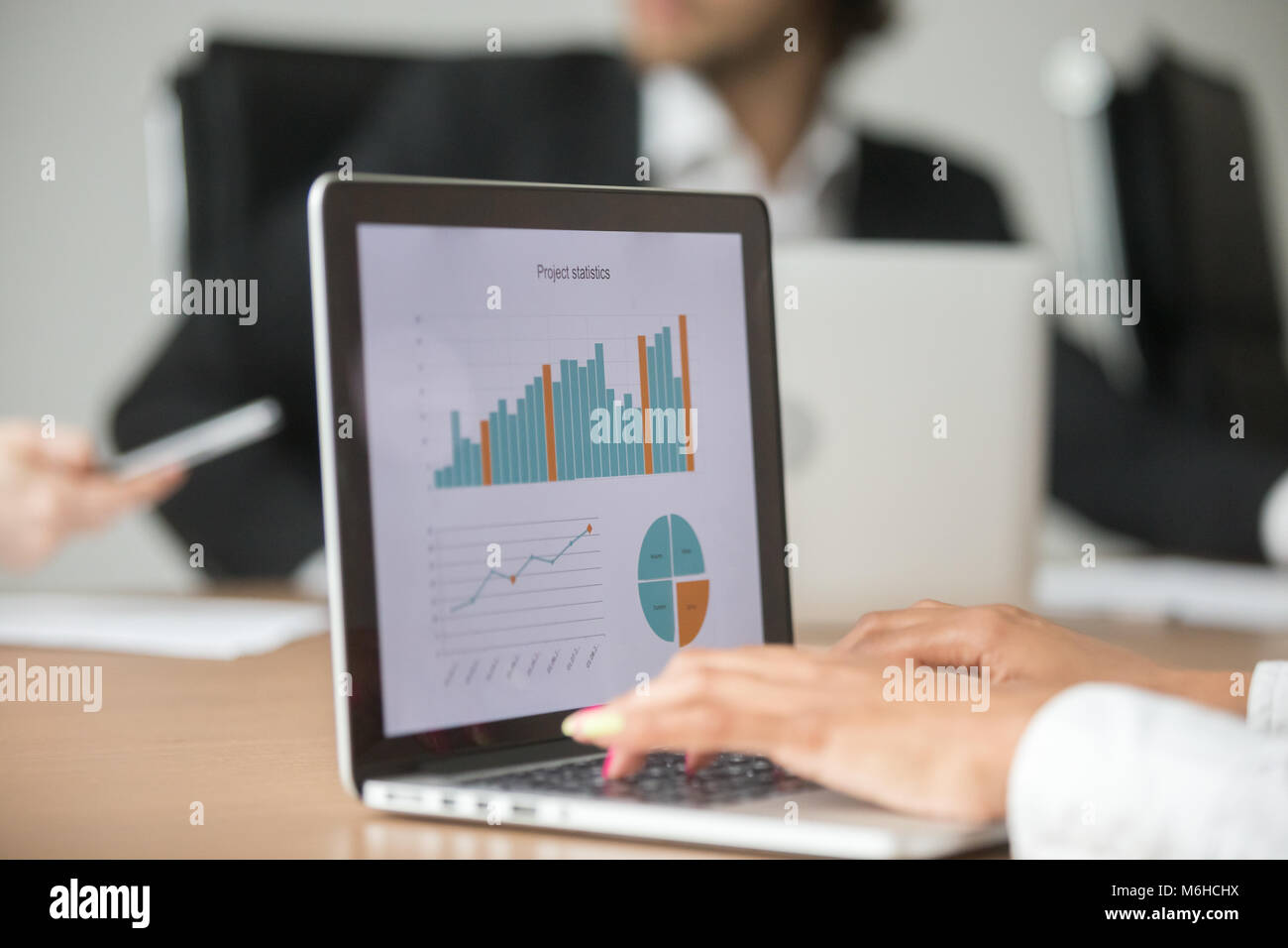 Businesswoman working with statistical report at team meeting an - Stock Image