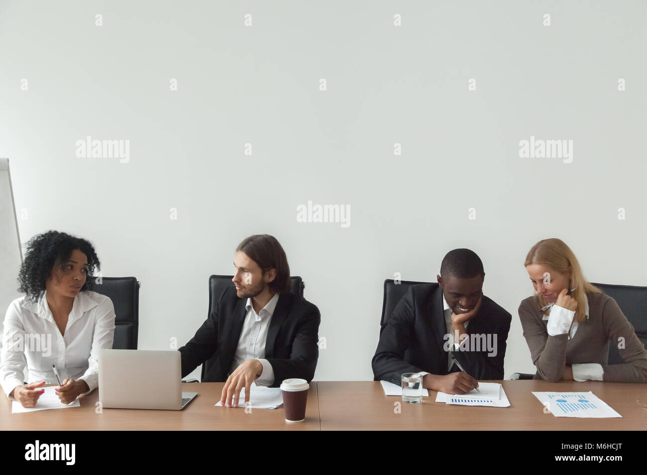 Diverse business people working talking at conference table, cor - Stock Image