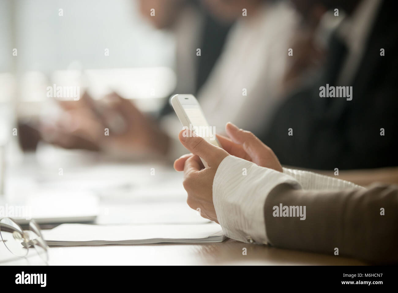 Businesswoman holding mobile phone at office meeting, close up v Stock Photo