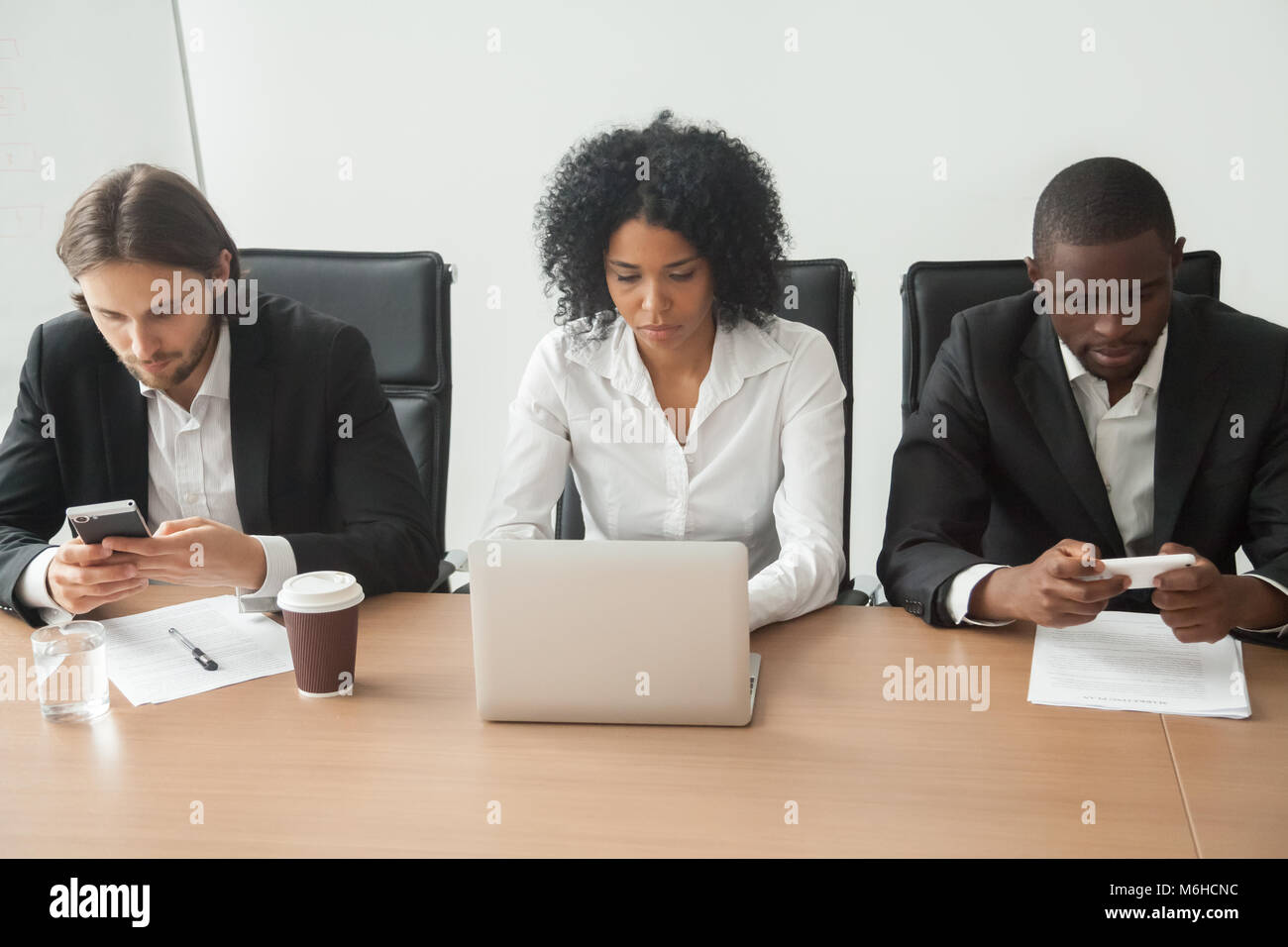 Multiracial business people sitting at office table using corpor Stock Photo