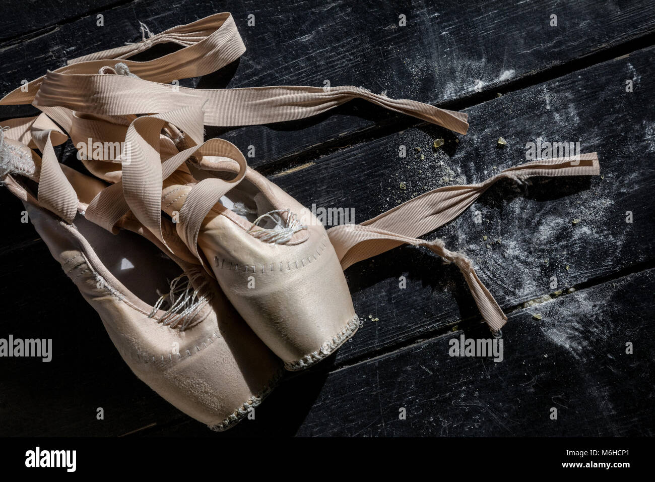 Pointe shoes on wooden background on theater stage - Stock Image