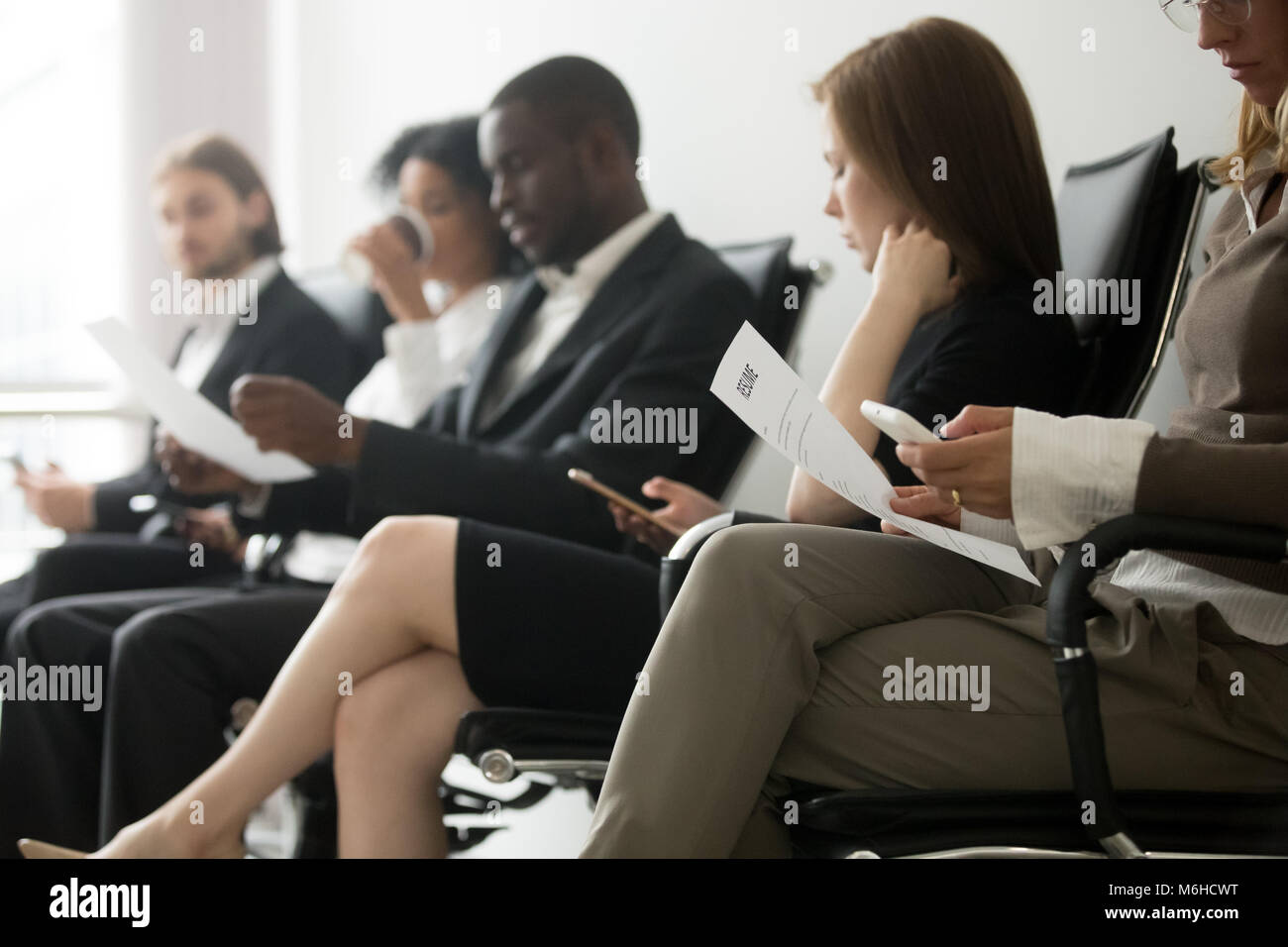 Multi-ethnic applicants sitting in queue waiting for job intervi - Stock Image