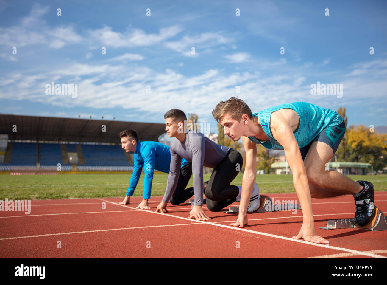 Athletes at the sprint start line in track and field - Stock Image