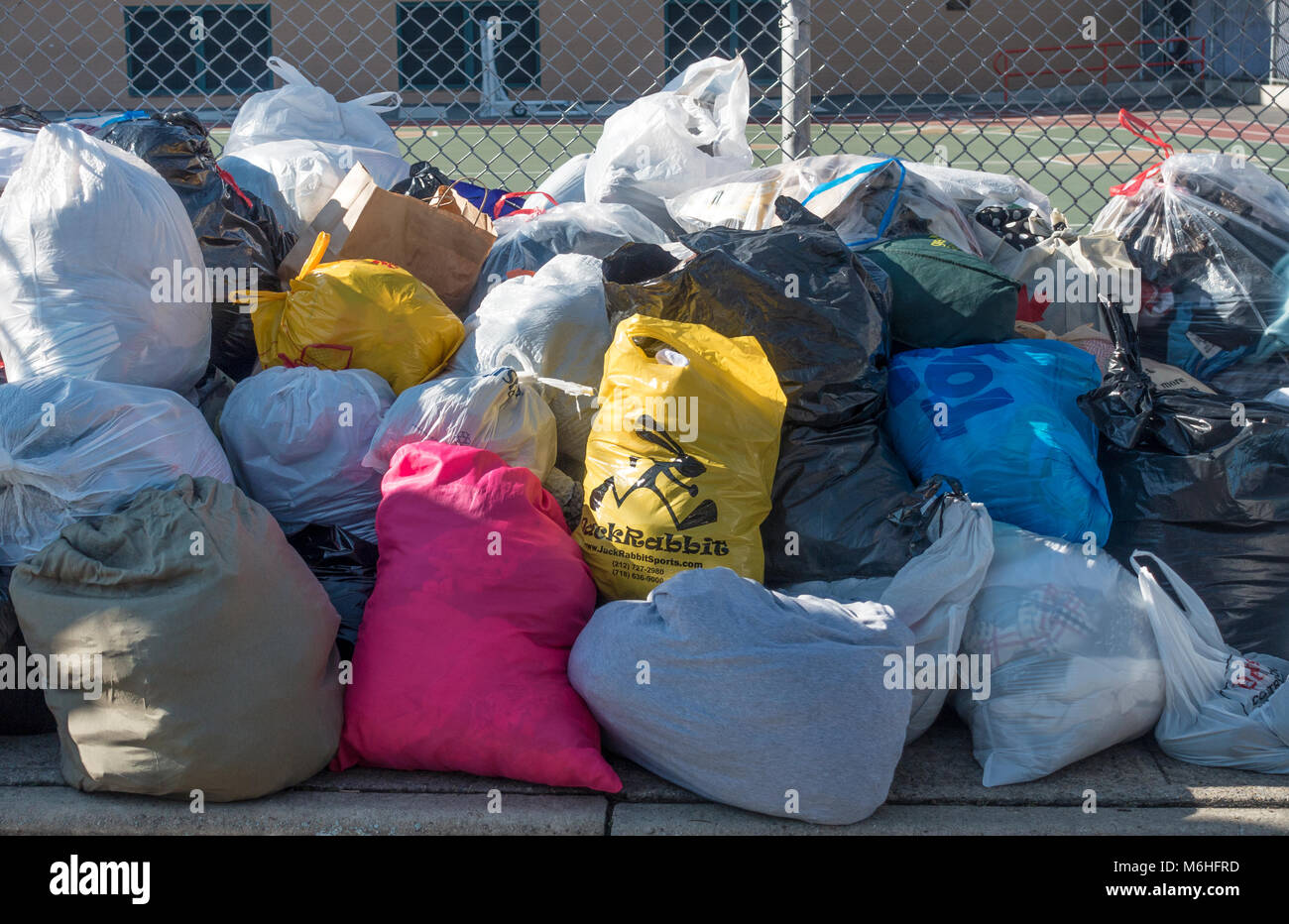 Bundles of used clothing left for distribution to the needy in Carroll Gardens, Brooklyn, NY - Stock Image