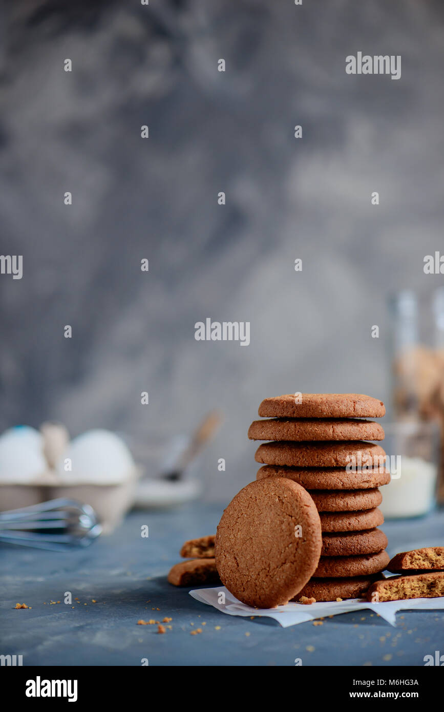 Oatmeal cookies in a neat stack on a stone background with baking ingredients out of focus. Cooking concept in high - Stock Image