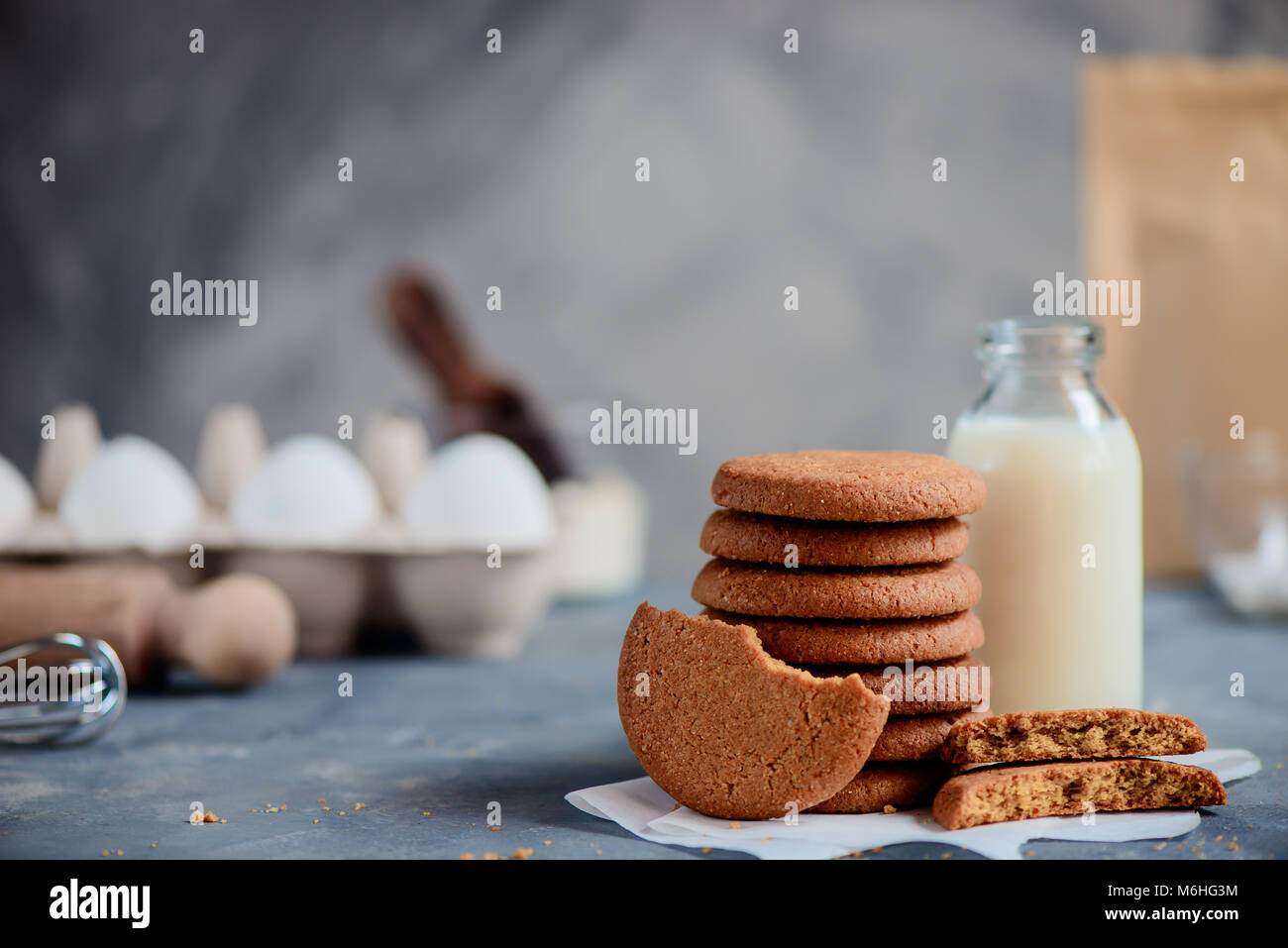 Oatmeal cookies in a neat stack with a milk bottle and baking ingredients out of focus. Baking concept in high key - Stock Image