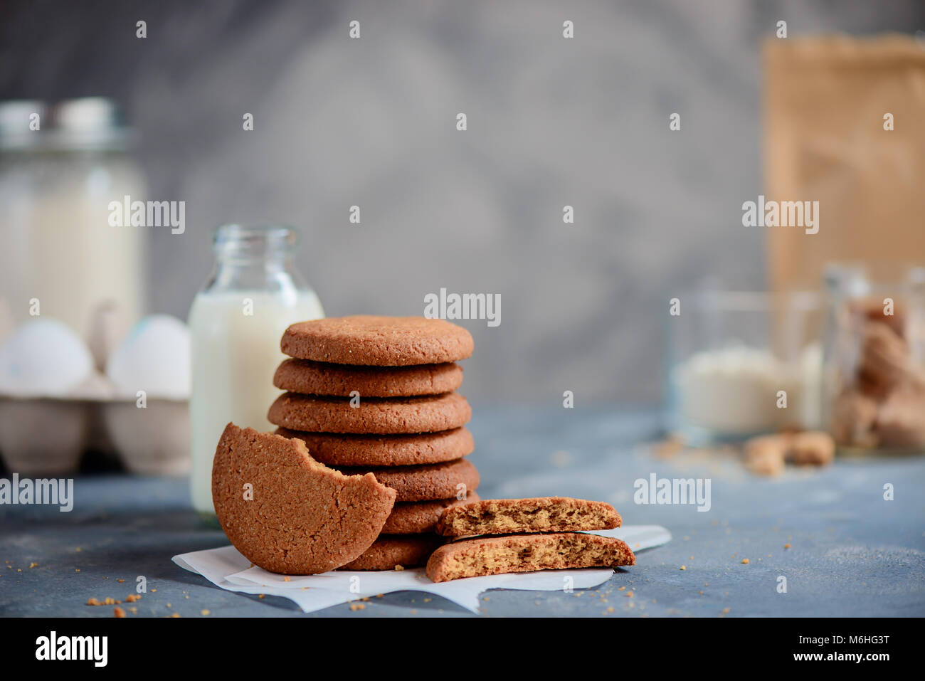 Stack of sugar buckwheat cookies on a stone background with baking ingredients out of focus. Cooking concept in - Stock Image