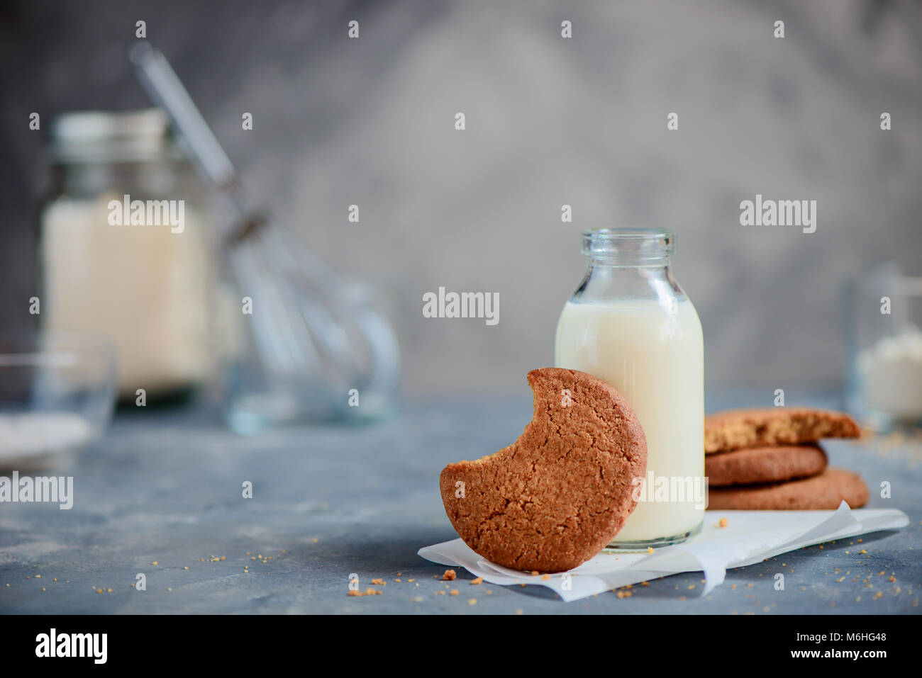 Tasty homemade pastry concept with copy space. Cookie with a bite mark on a kitchen table with a milk bottle and - Stock Image