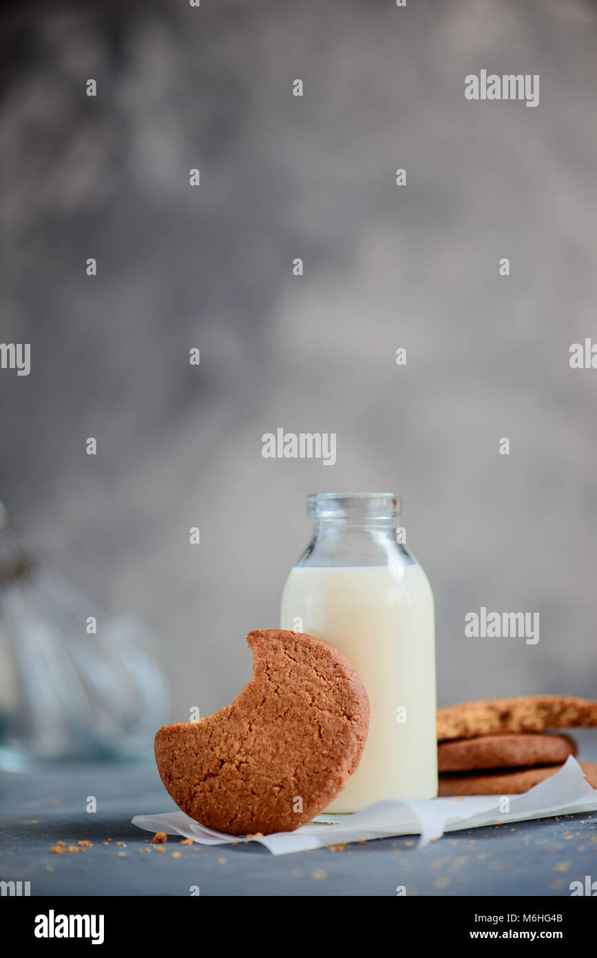 Cookie with a bite mark on a kitchen table with a milk bottle and baking ingredients out of focus. Tasty homemade - Stock Image