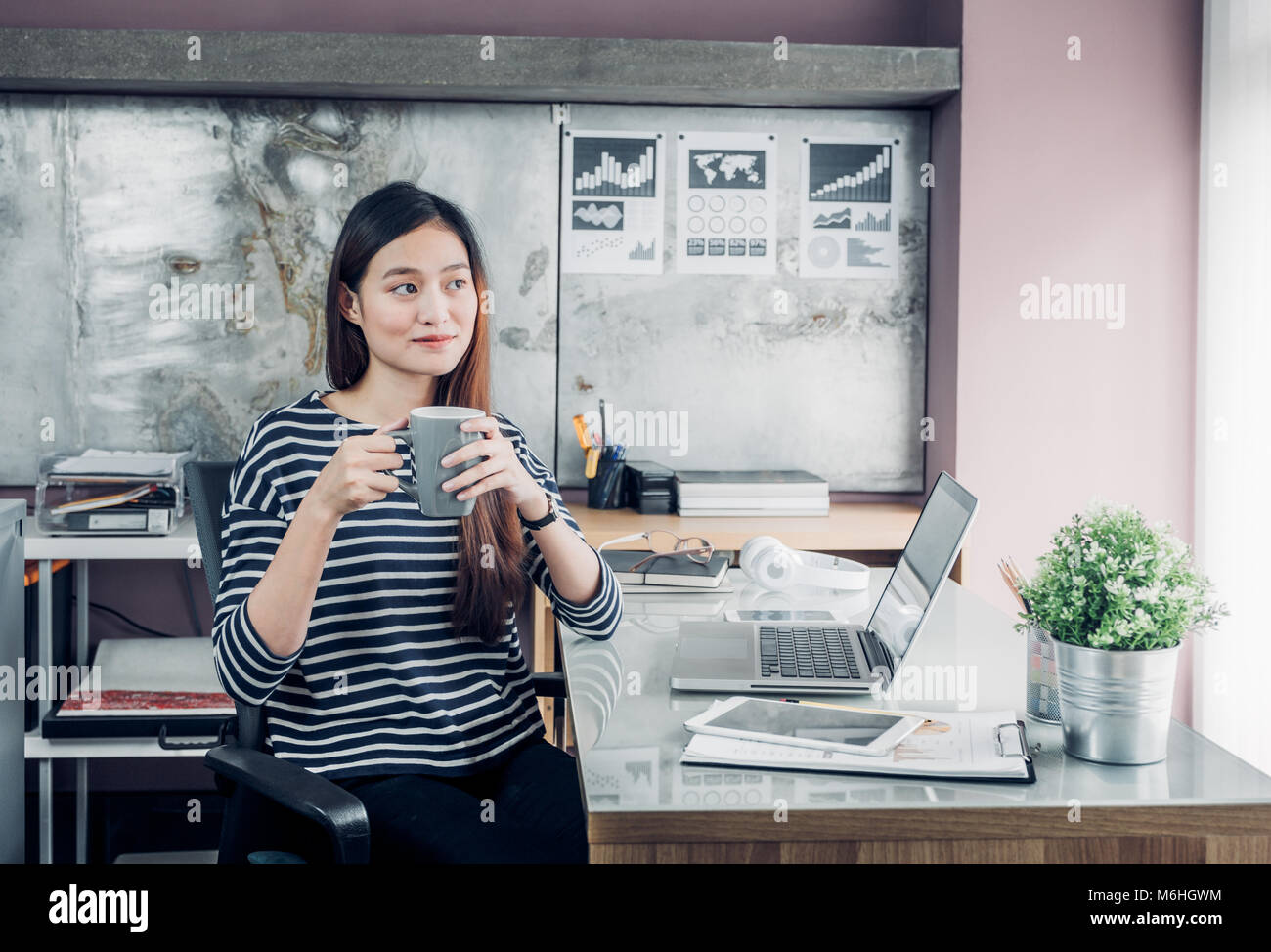 Asian businesswoman take a coffee break after working with smiling face,Happy office life concept,working woman - Stock Image