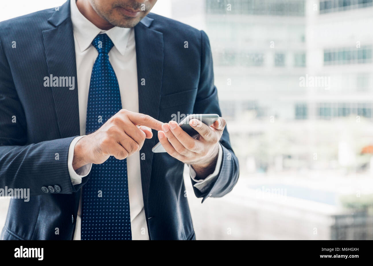 close up hand of businessman using mobile phone near office window at office building,online business concept. Stock Photo