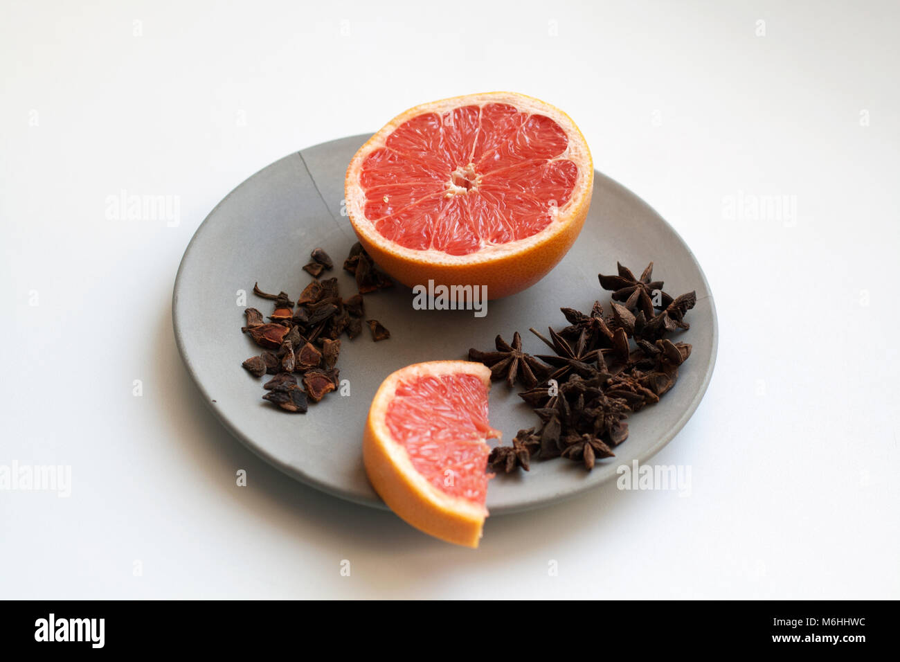 Fresh grapefruit slices and heap of star anise species isolated on grey concrete plate - Stock Image