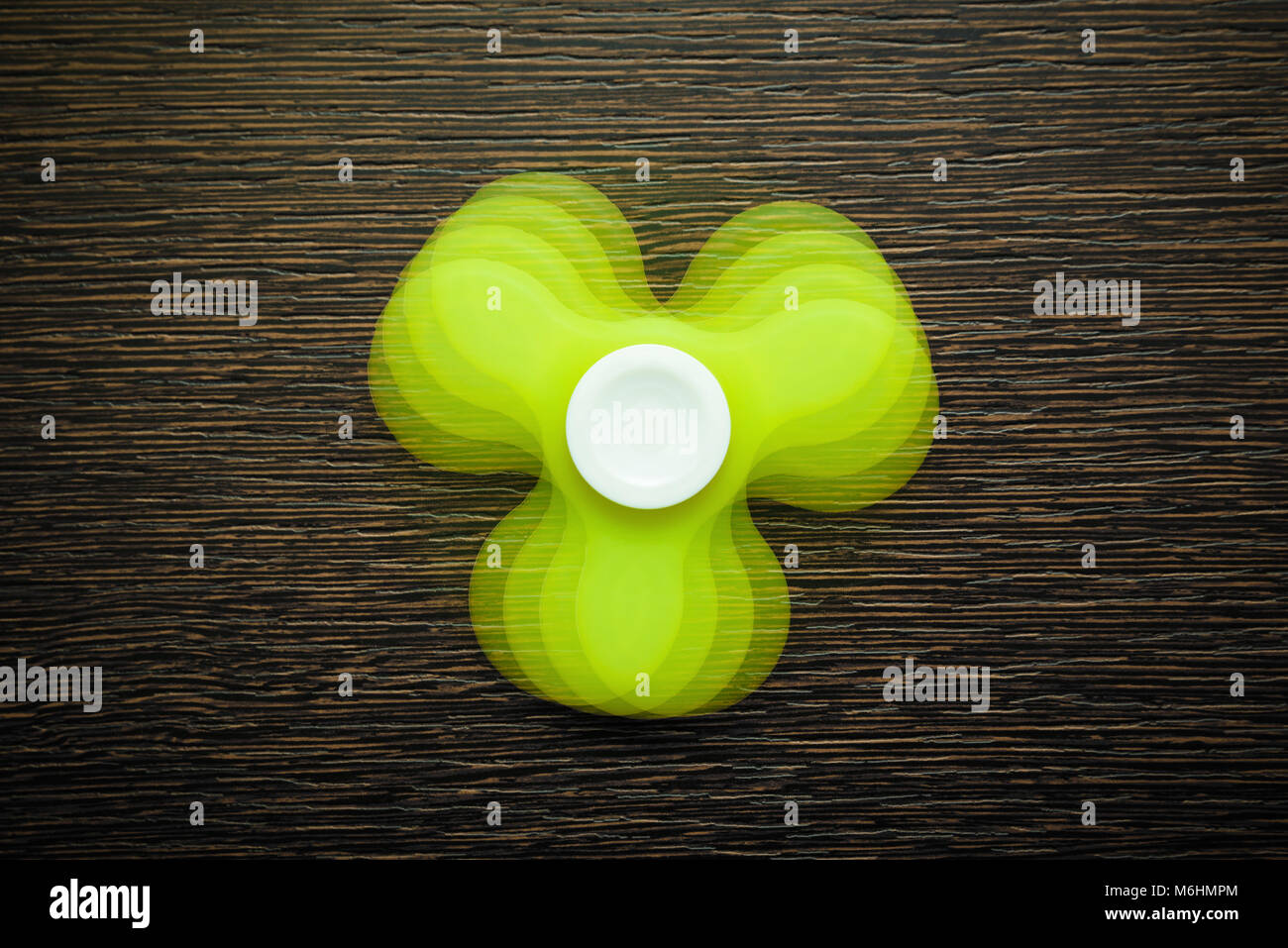 Green fidget spinner spinning on wooden table, shot with repeating flash for stroboscopic effect - Stock Image