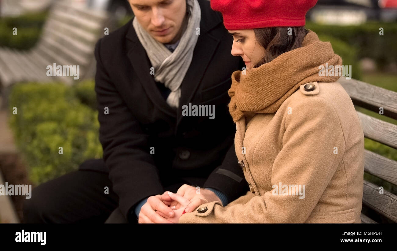 Young husband supporting his beloved wife, health and psychological problems - Stock Image