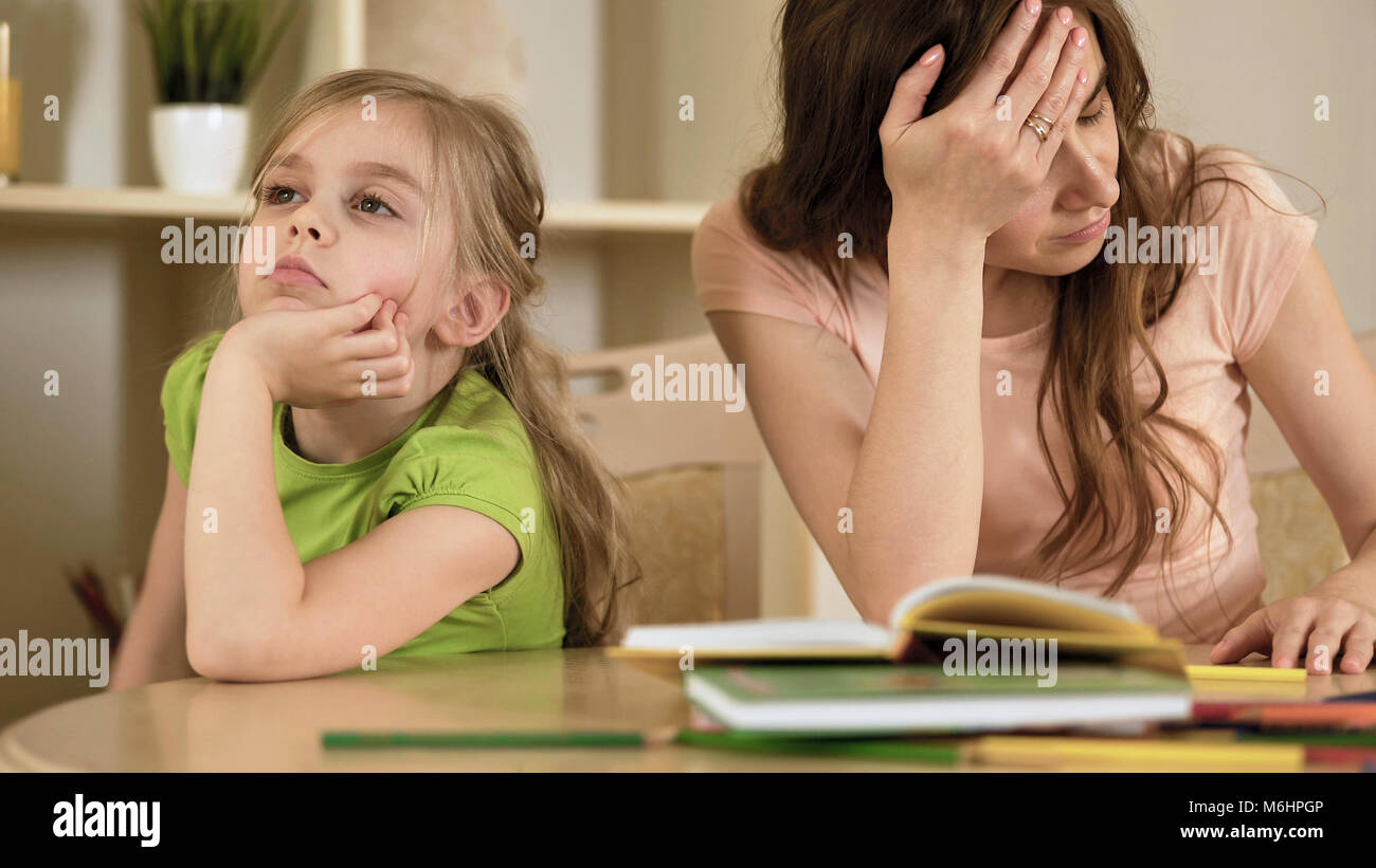 Upset mother is angry to little bored daughter, homeschooling, misunderstanding - Stock Image