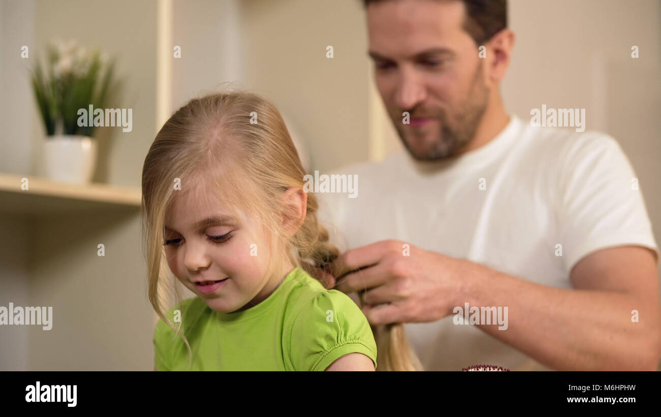 Happy single father braiding daughter's hair, taking care of beloved little girl - Stock Image
