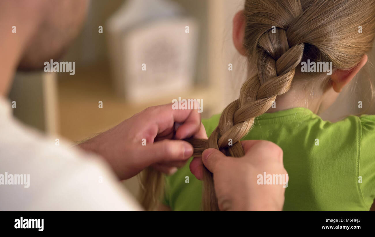 Father braiding daughters hair carefully, taking care of beloved kid, family - Stock Image