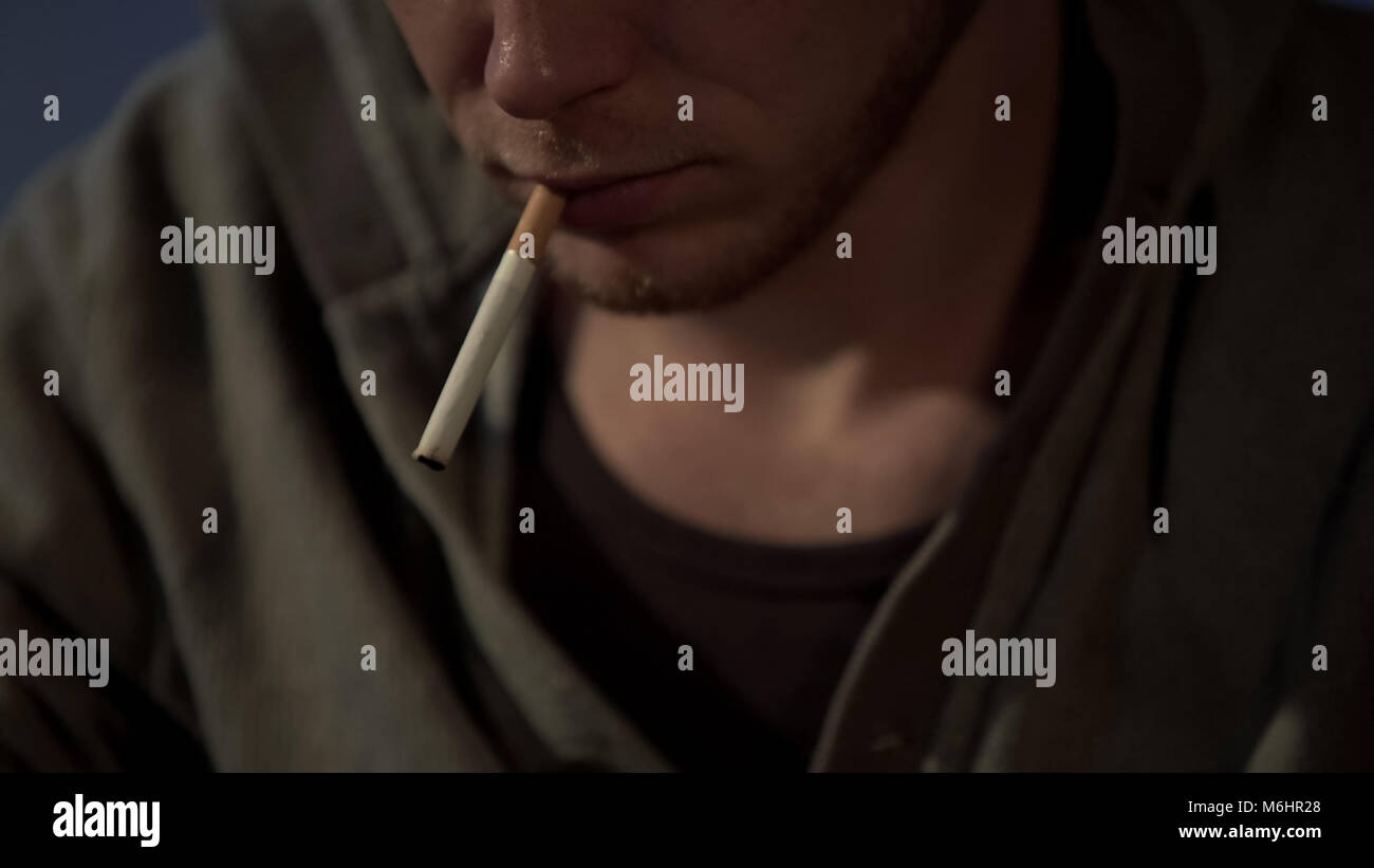 Young man smokes cigarette, depressed and abandoned, health risks, close up - Stock Image