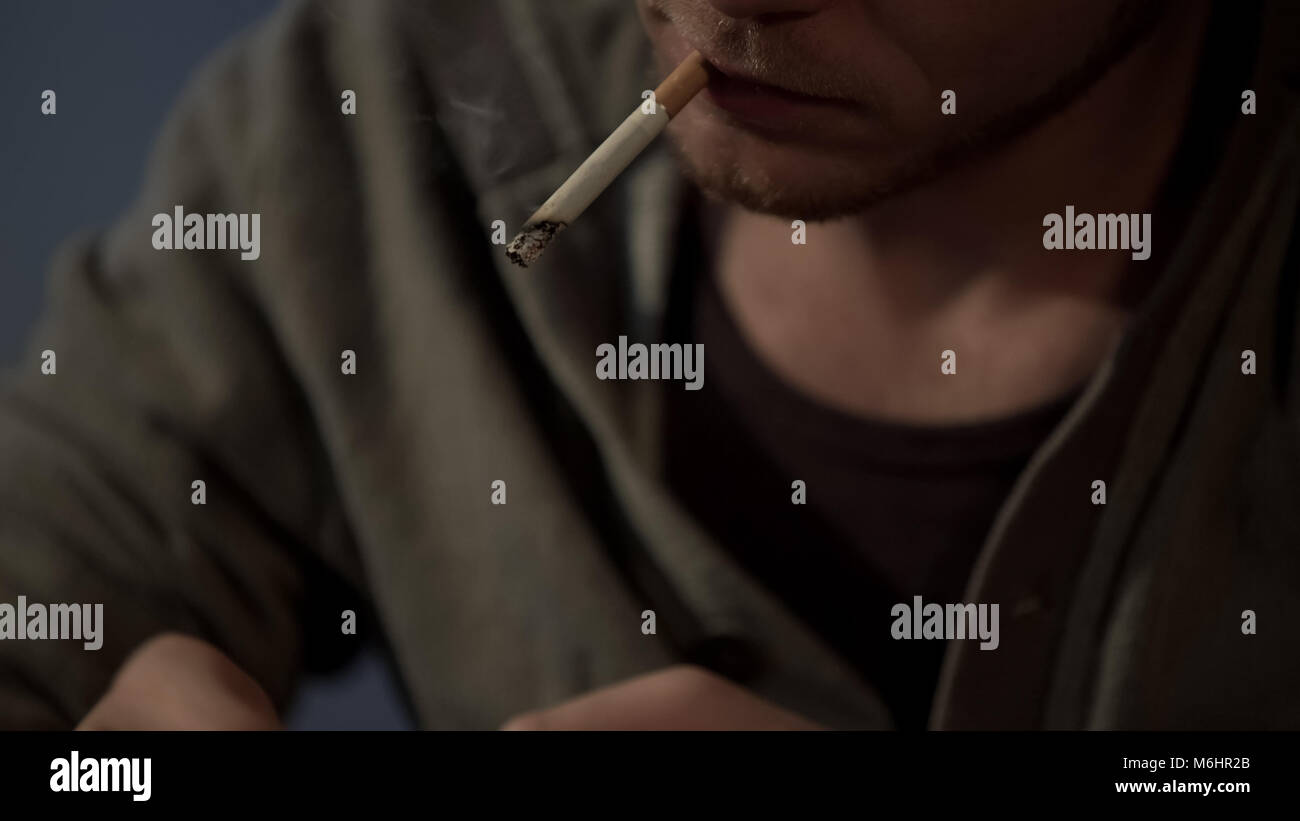 Depressed man smoking cigarette, life problems make nervous, addicted closeup - Stock Image